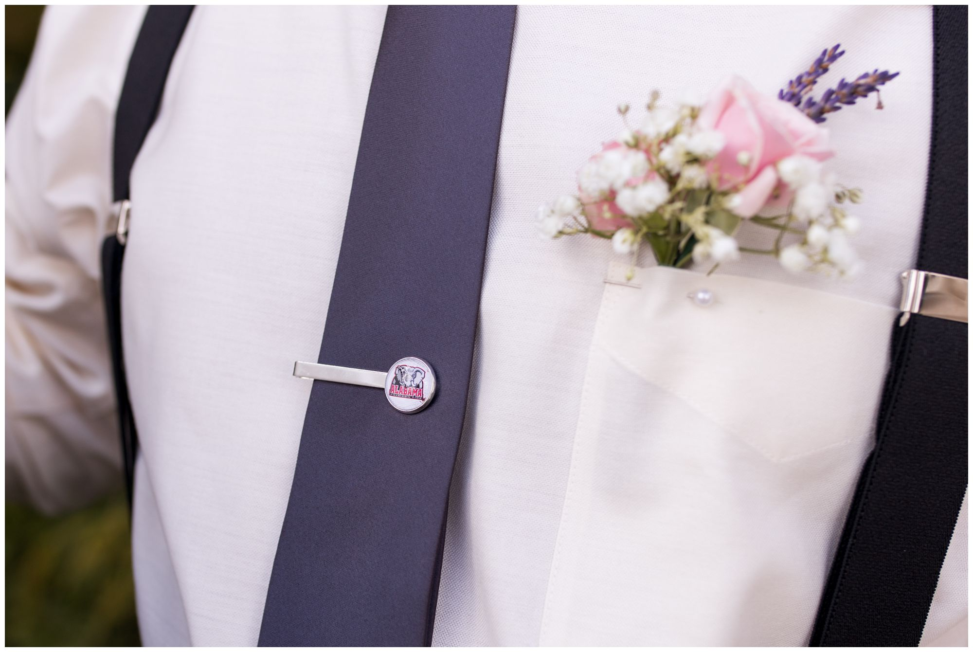 close up of groomsman's Alabama tie clip and boutonniere