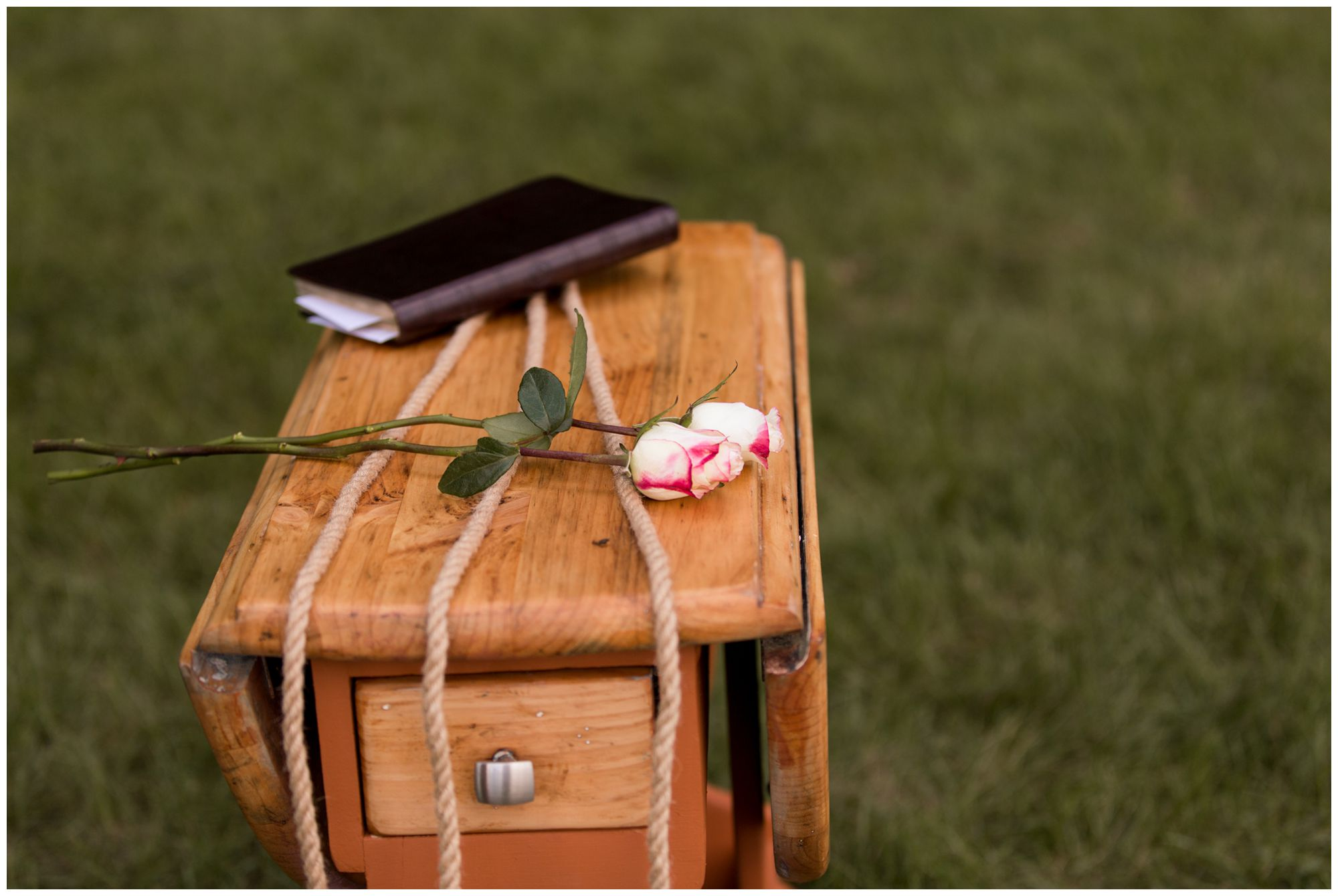 pink roses and bible lying over cord strands for unity ceremony
