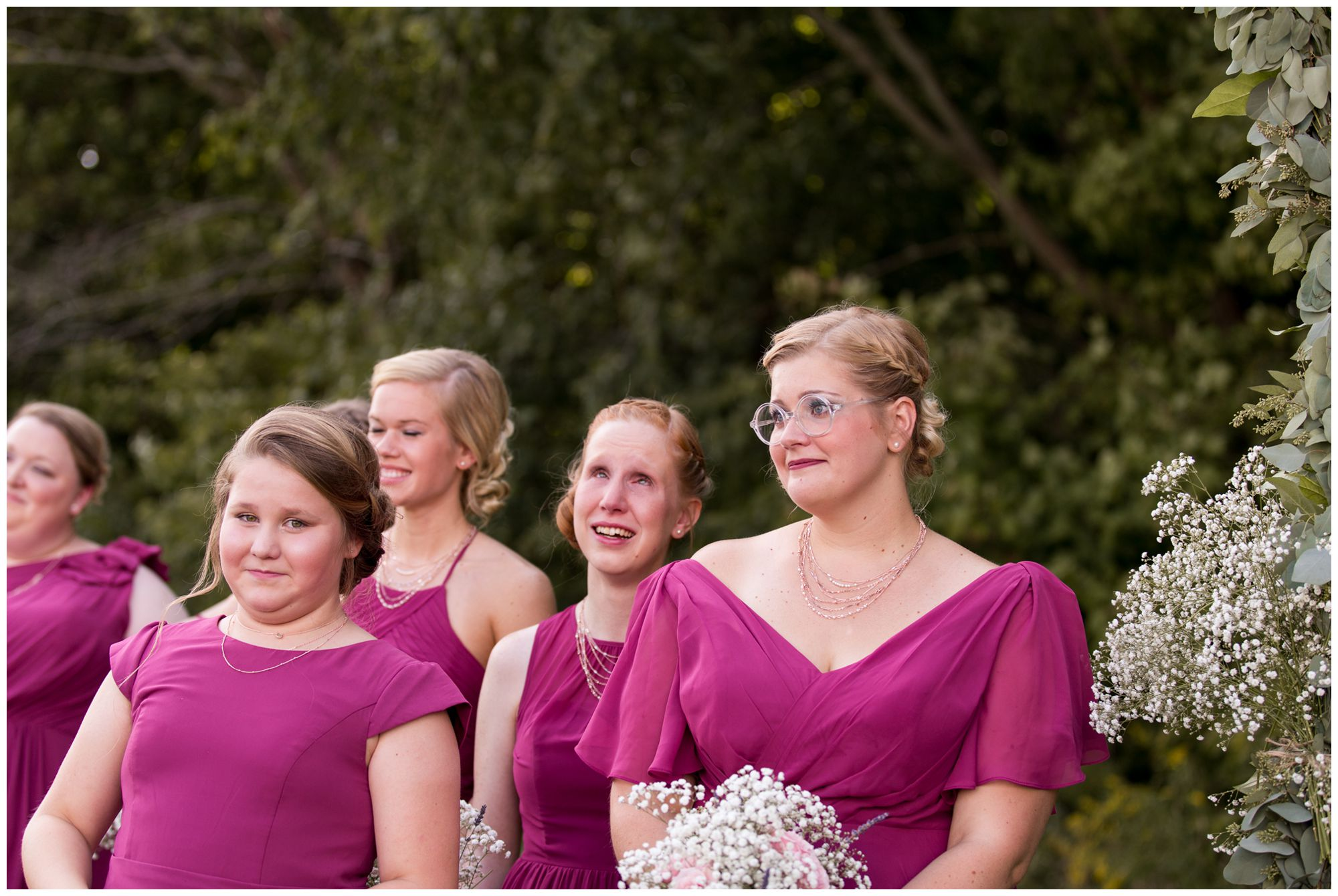 maid of honor, flower girl, and bridesmaids look on at bride Tabea as she comes down the aisle during Crossroads Community Church wedding