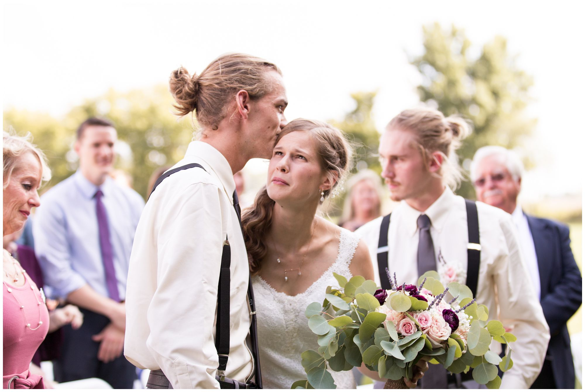 bride Tabea tears up as brother kisses side of head at end of aisle