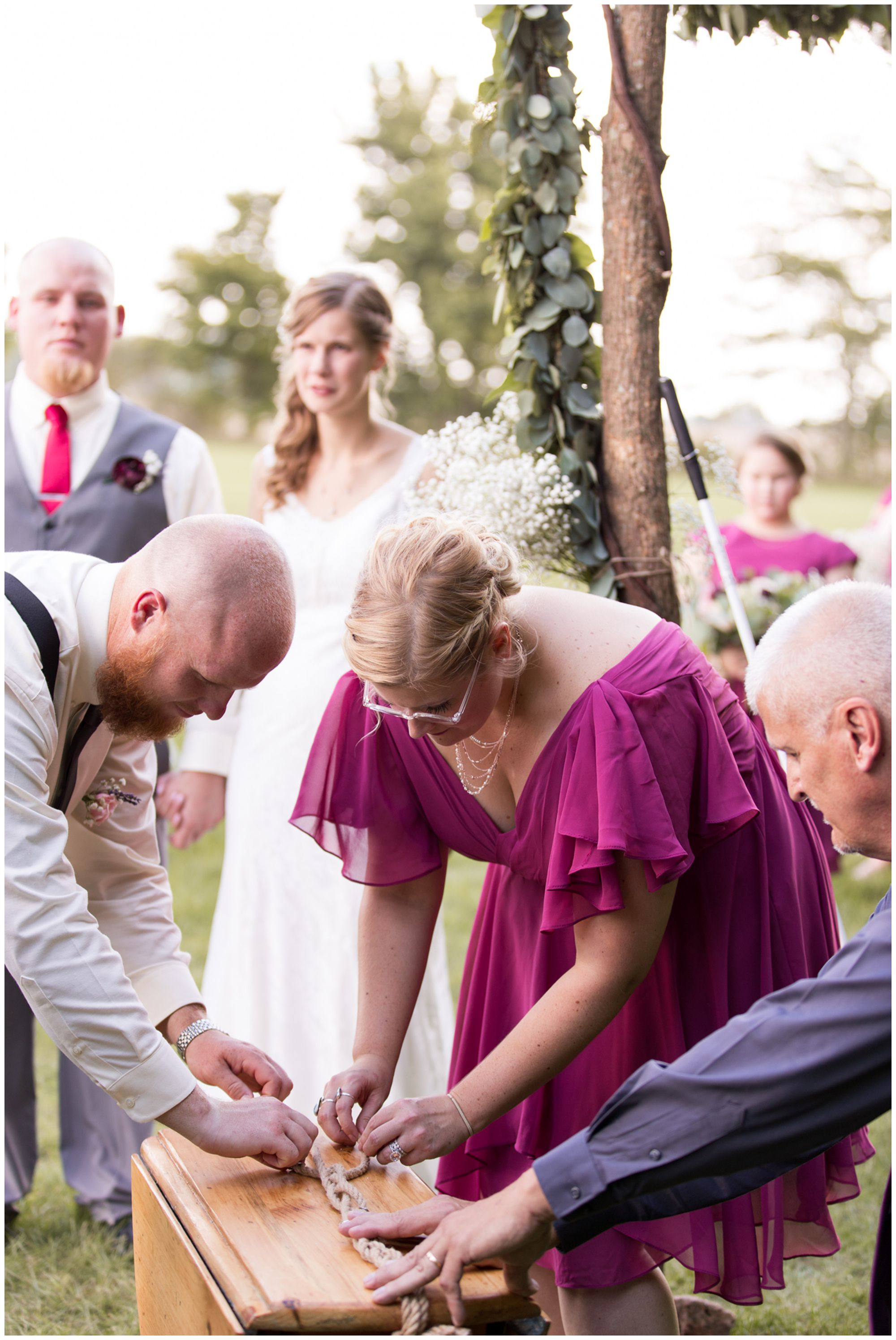 bride's sister Becca and groom's brother Ben add charm and finish knotting the cord during wedding ceremony at Crossroads Community Church