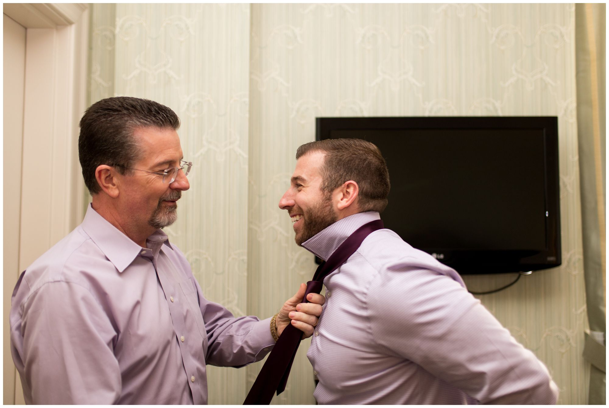 groom's father ties groom's tie on morning of Wabash Indiana wedding at Charley Creek Inn