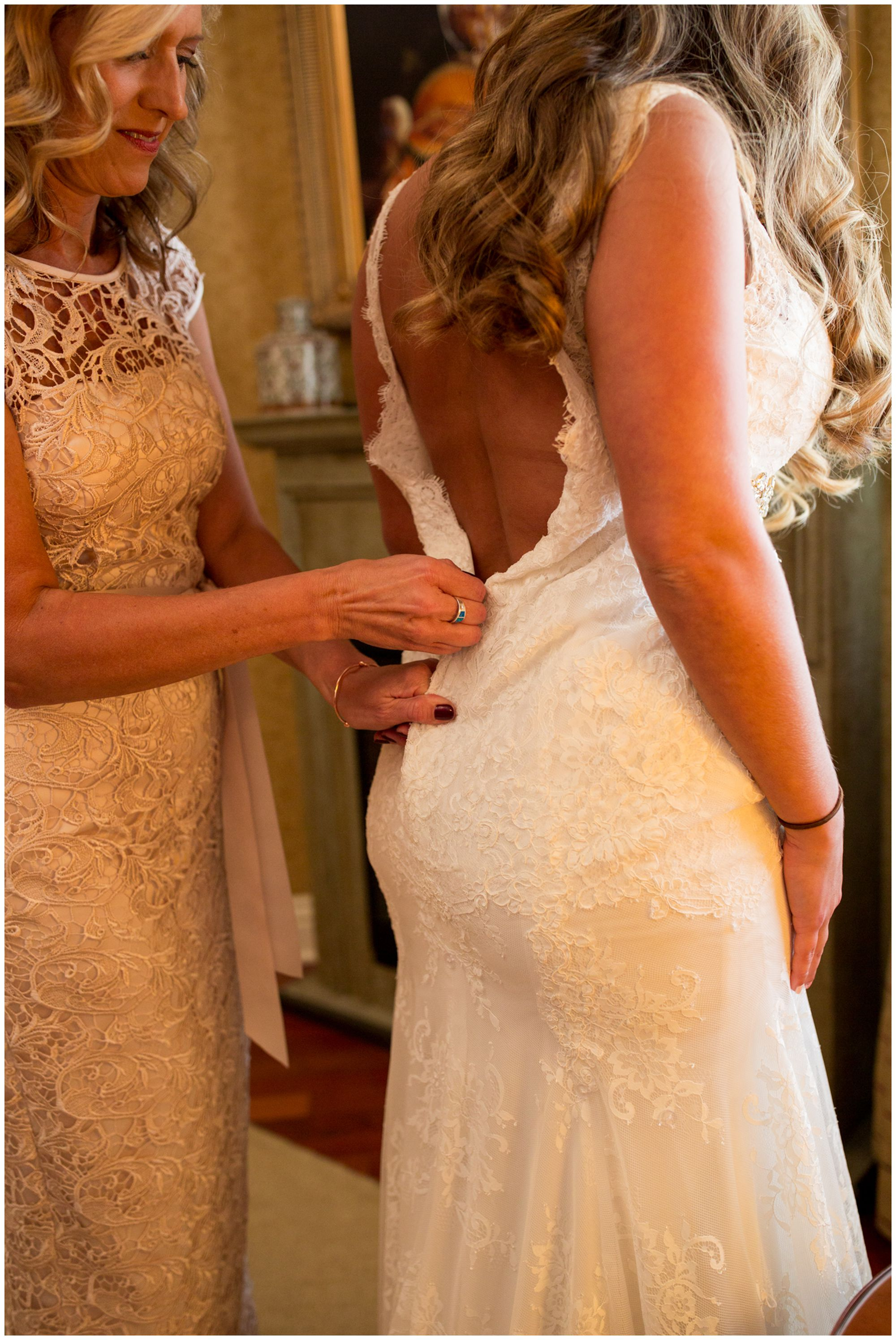 bride's mom zips the back of bride's dress before Wabash Indiana wedding at Charley Creek Inn