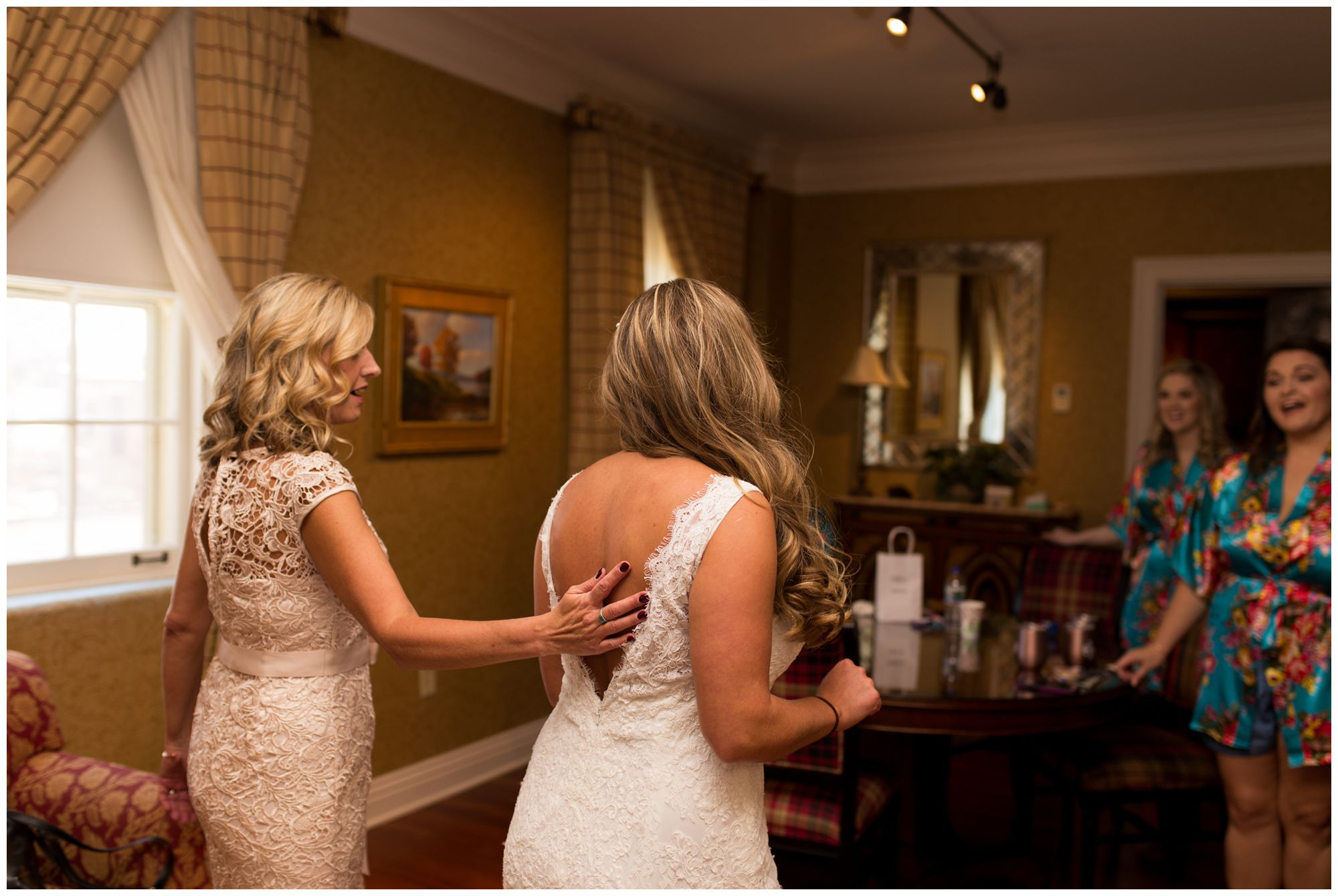 bride's mom puts hand on small of bride's back as bridesmaids look on at Charley Creek Inn in Wabash Indiana