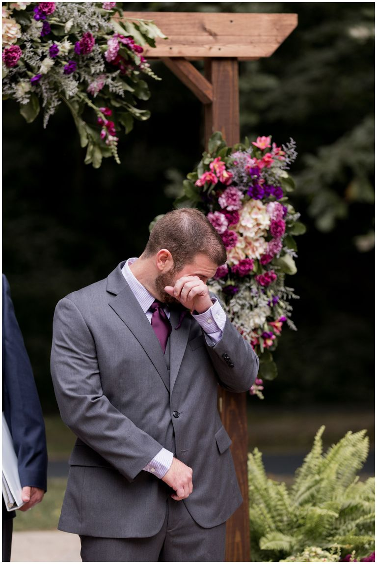 groom wipes away tears at Charley Creek Gardens during Wabash Indiana wedding ceremony