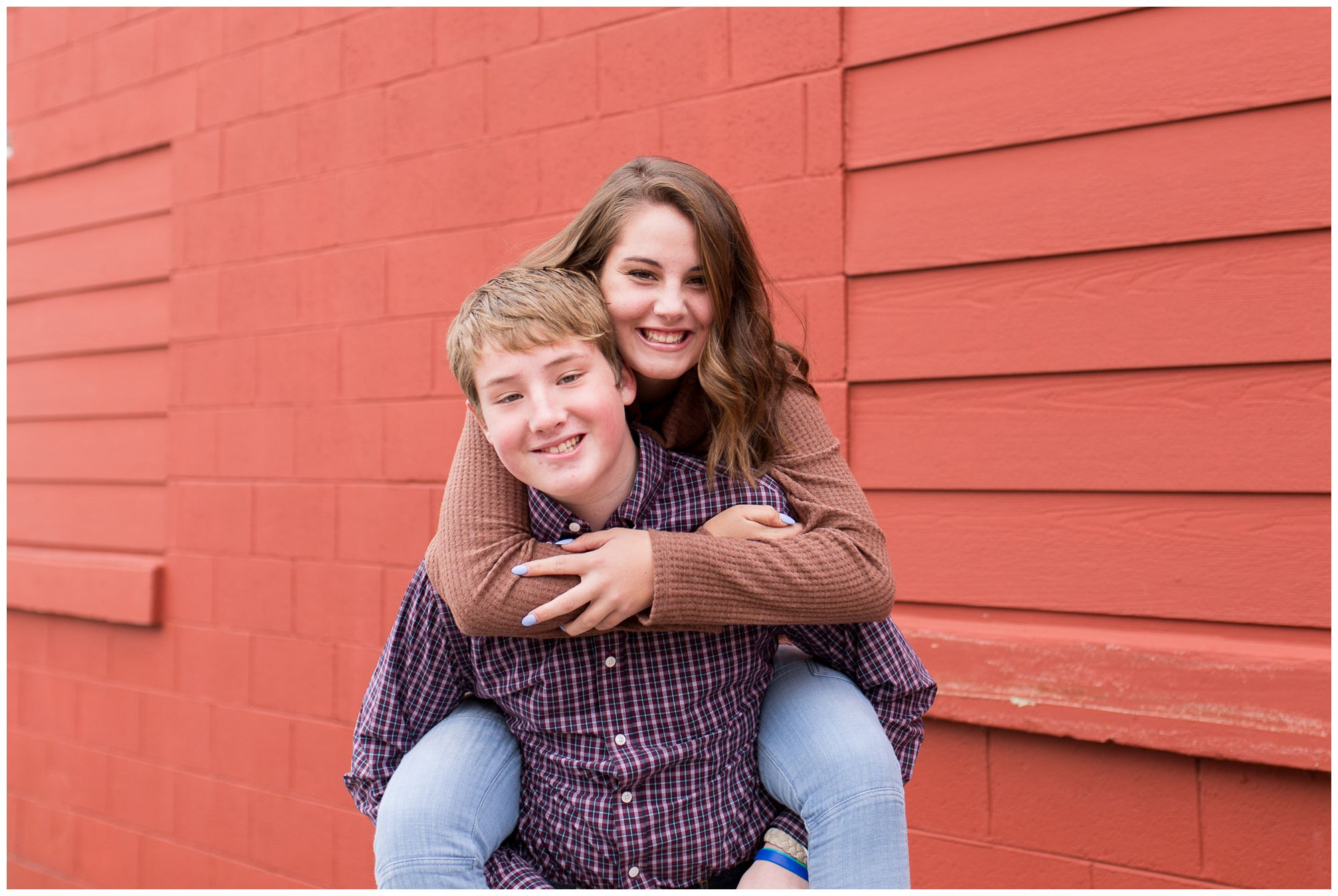 sister on brother's back during downtown Zionsville family photos