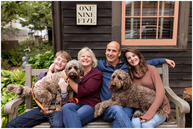 family holding dogs on bench during family session in downtown Zionsville