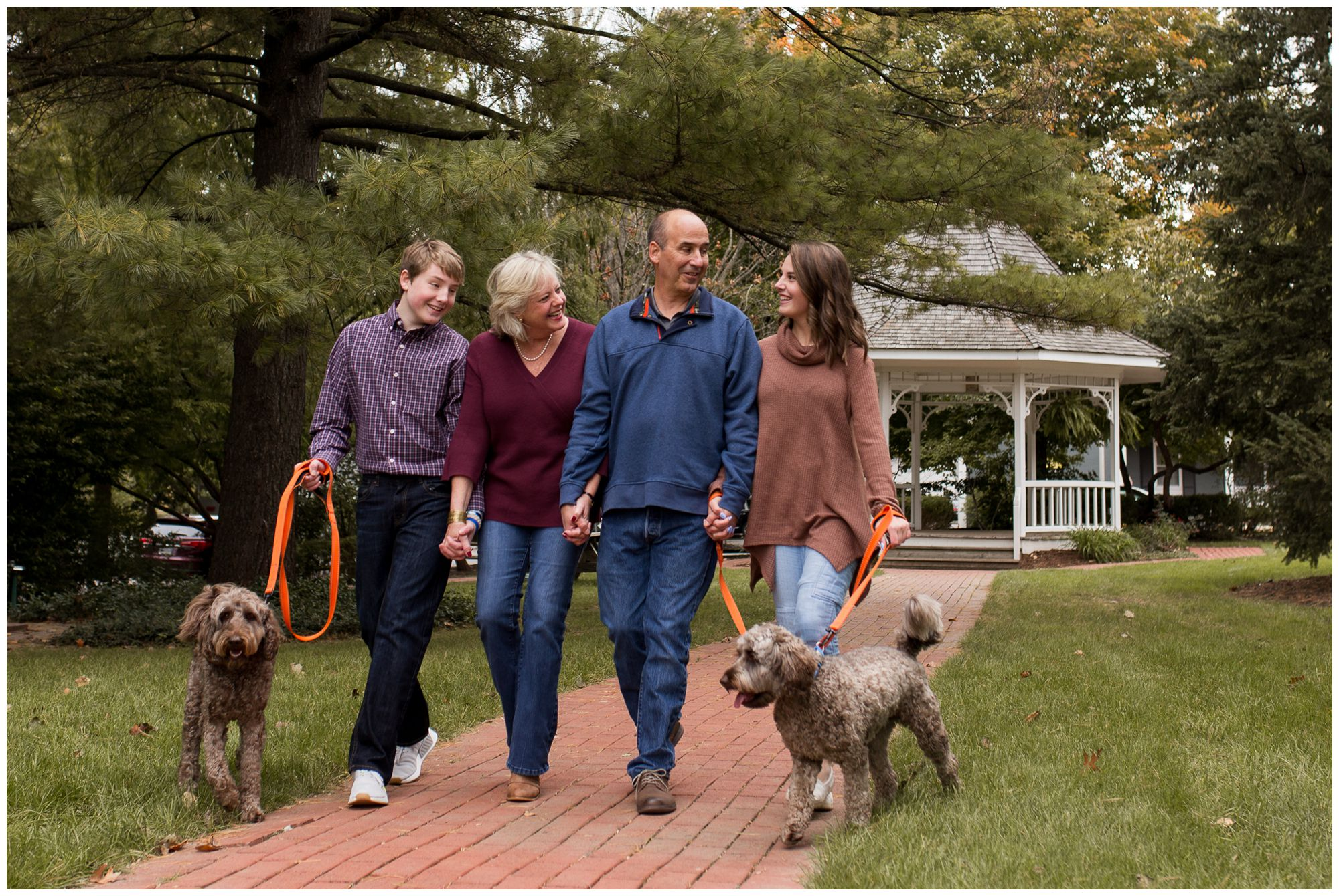 family walks dogs together during downtown Zionsville family session