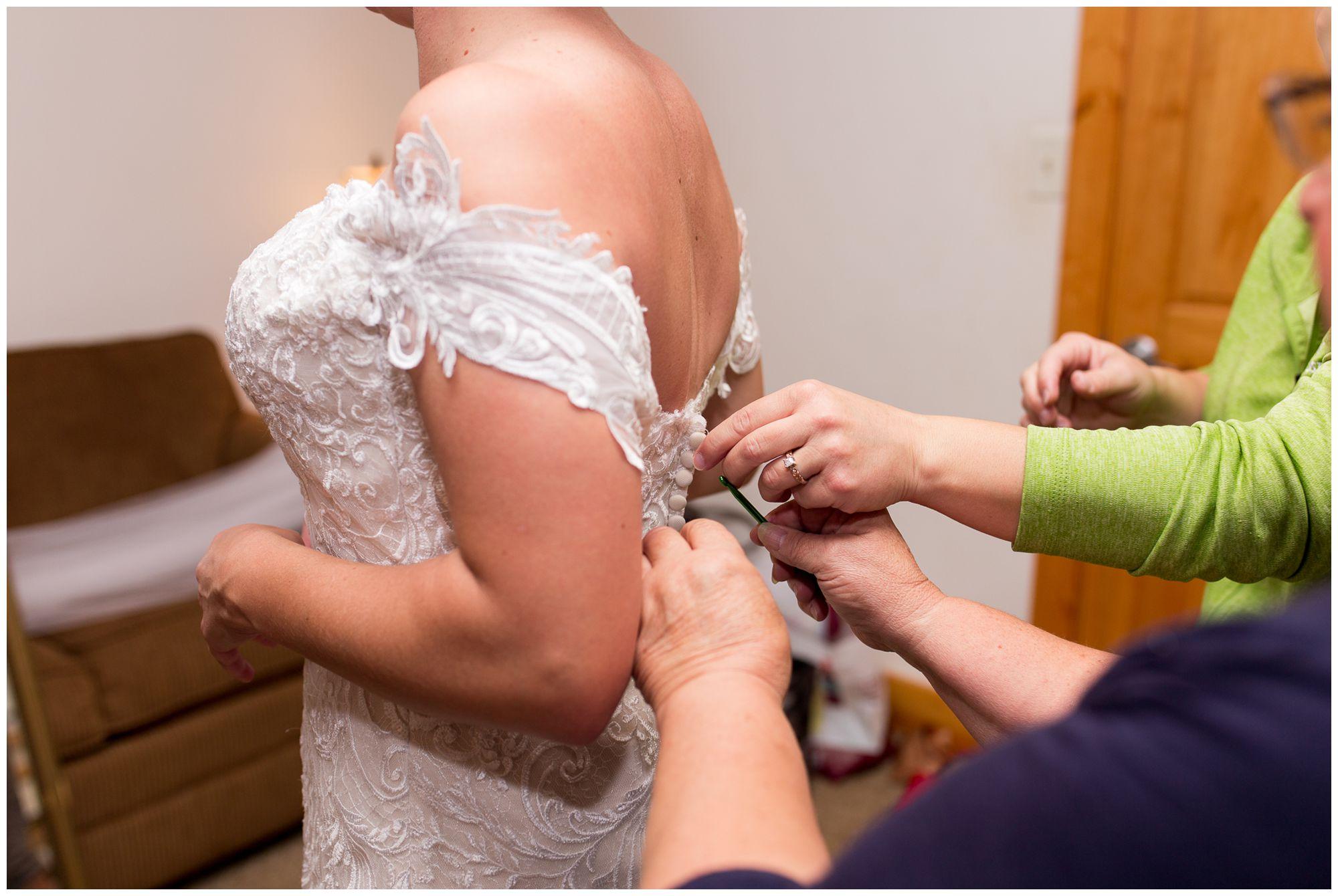 bride gets buttoned into dress before Peru Indiana wedding ceremony