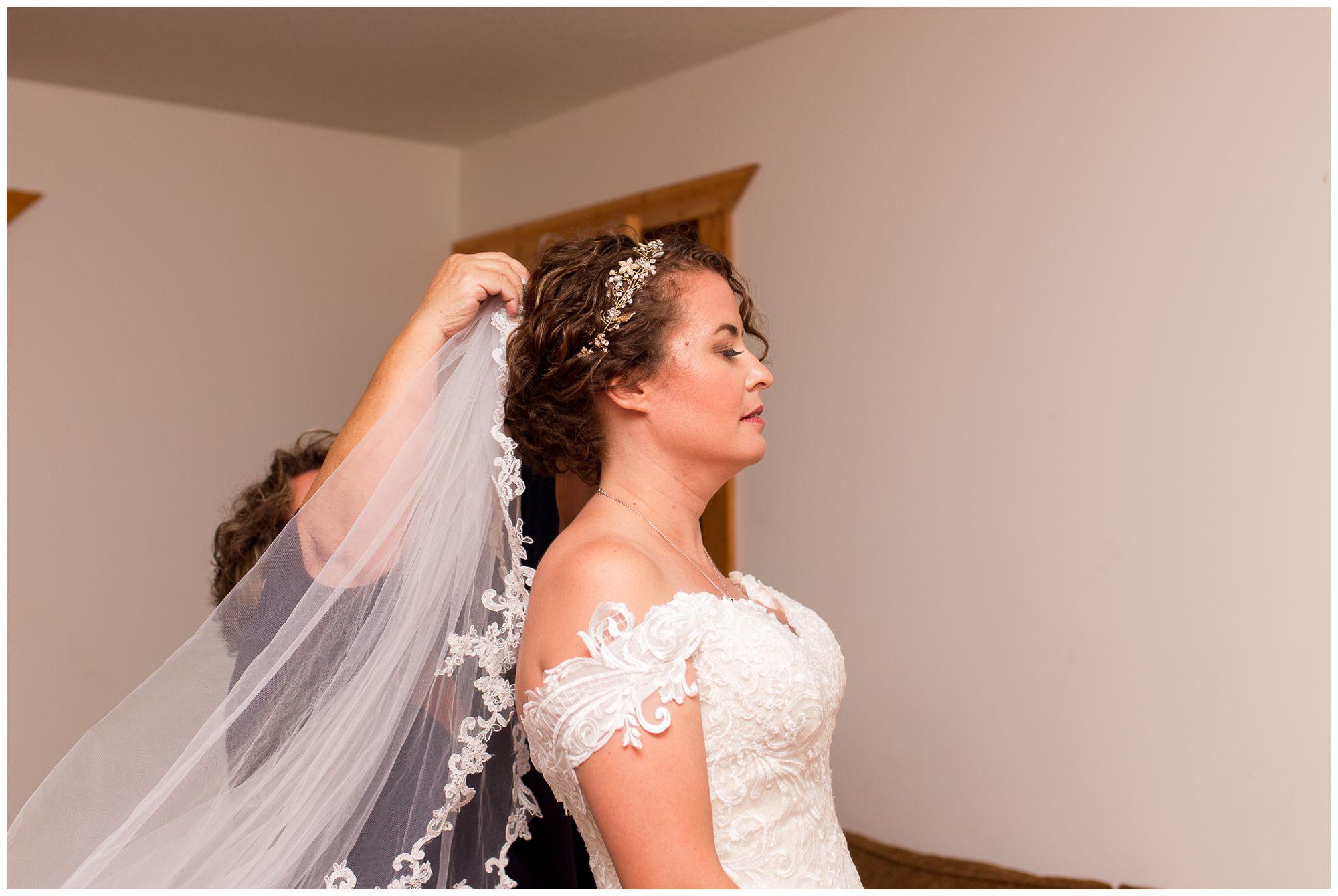 bride's mom puts on bride's veil before wedding in Peru Indiana