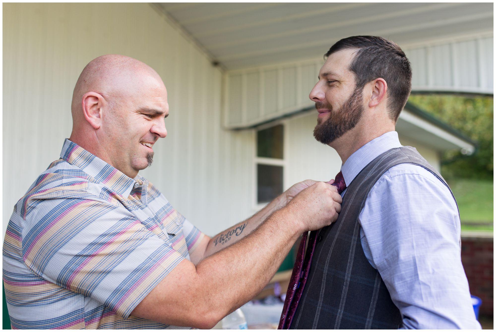 tying groom's tie before wedding first look in Peru Indiana