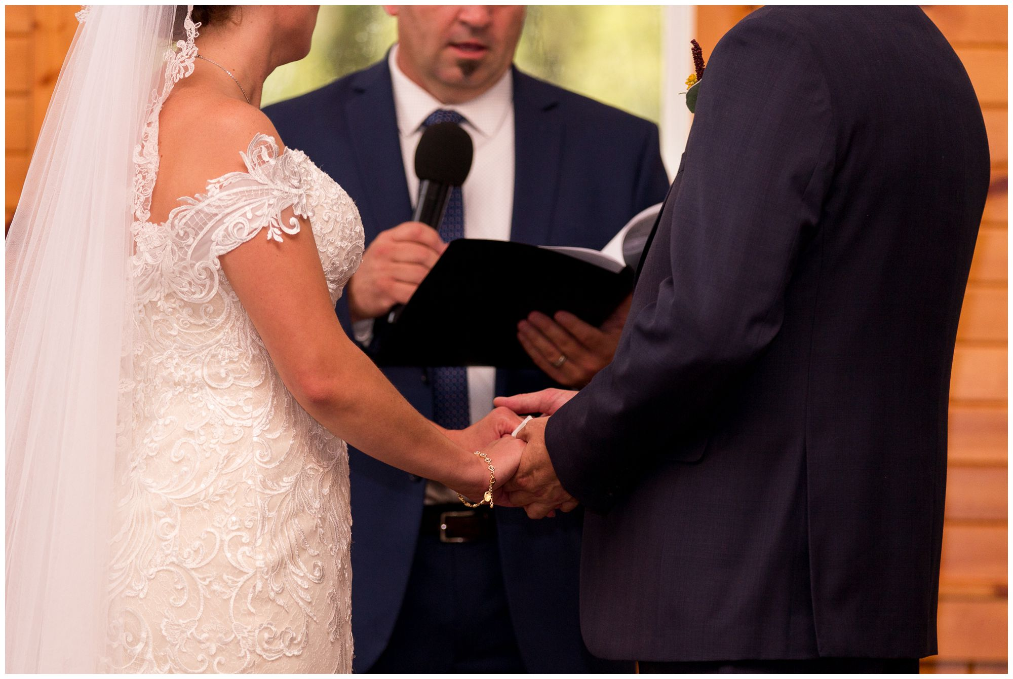 bride and groom hold hands during wedding ceremony at Western Howard Conservation Club in Peru Indiana
