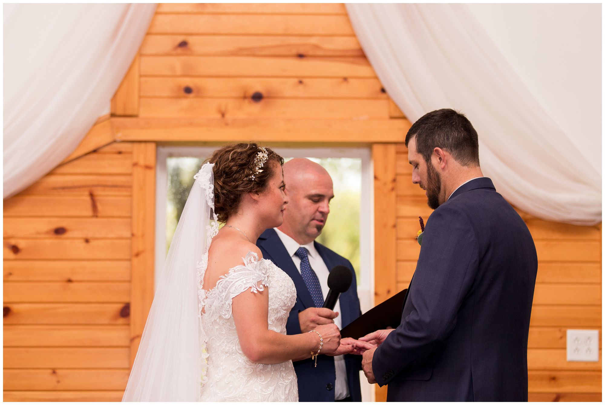 bride puts ring on groom's finger during Peru Indiana wedding ceremony