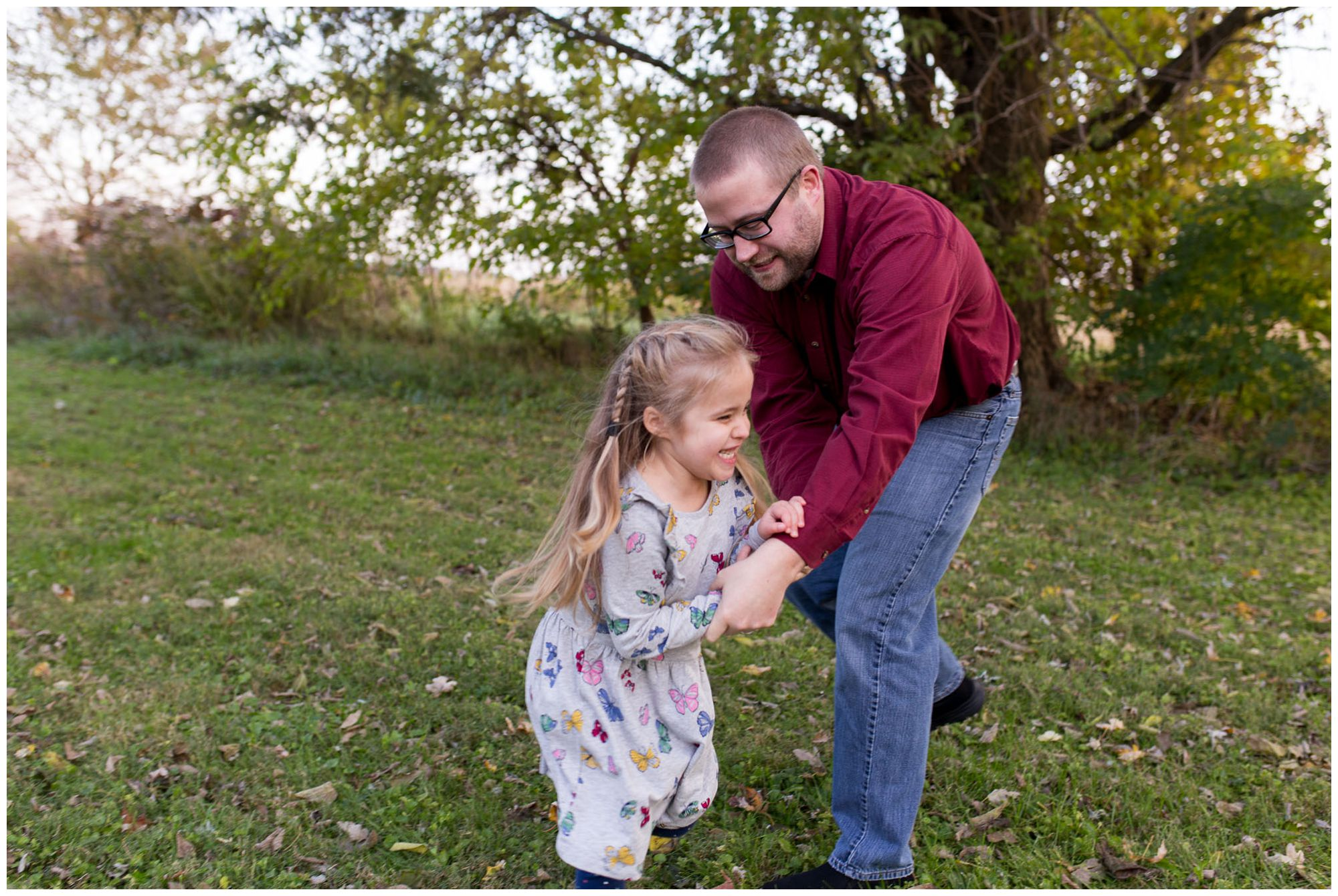dad chases daughter around during Kokomo family session at Wildkat Creek Reservoir Park