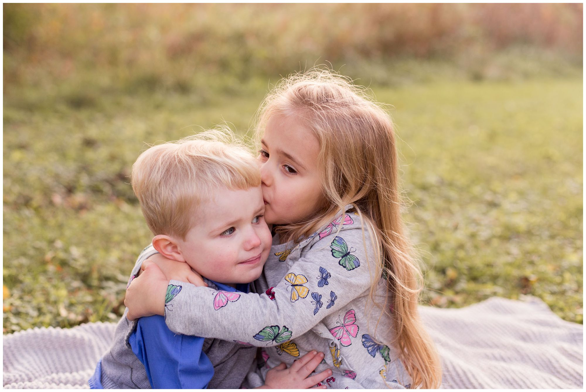sister kisses brother's forehead during family session by Kokomo family photographer