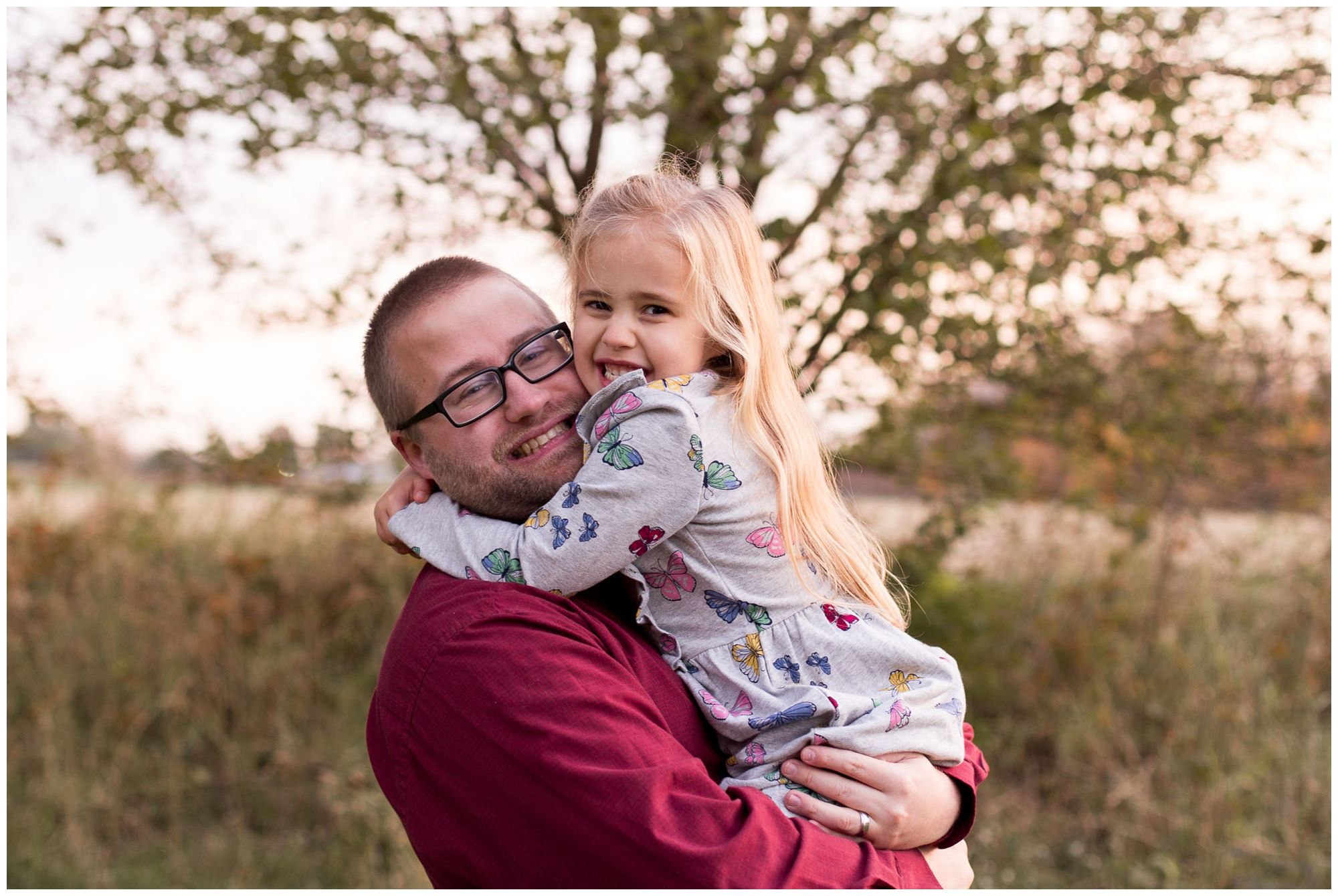 dad hugs daughter tight during family session at Kokomo Reservoir Park