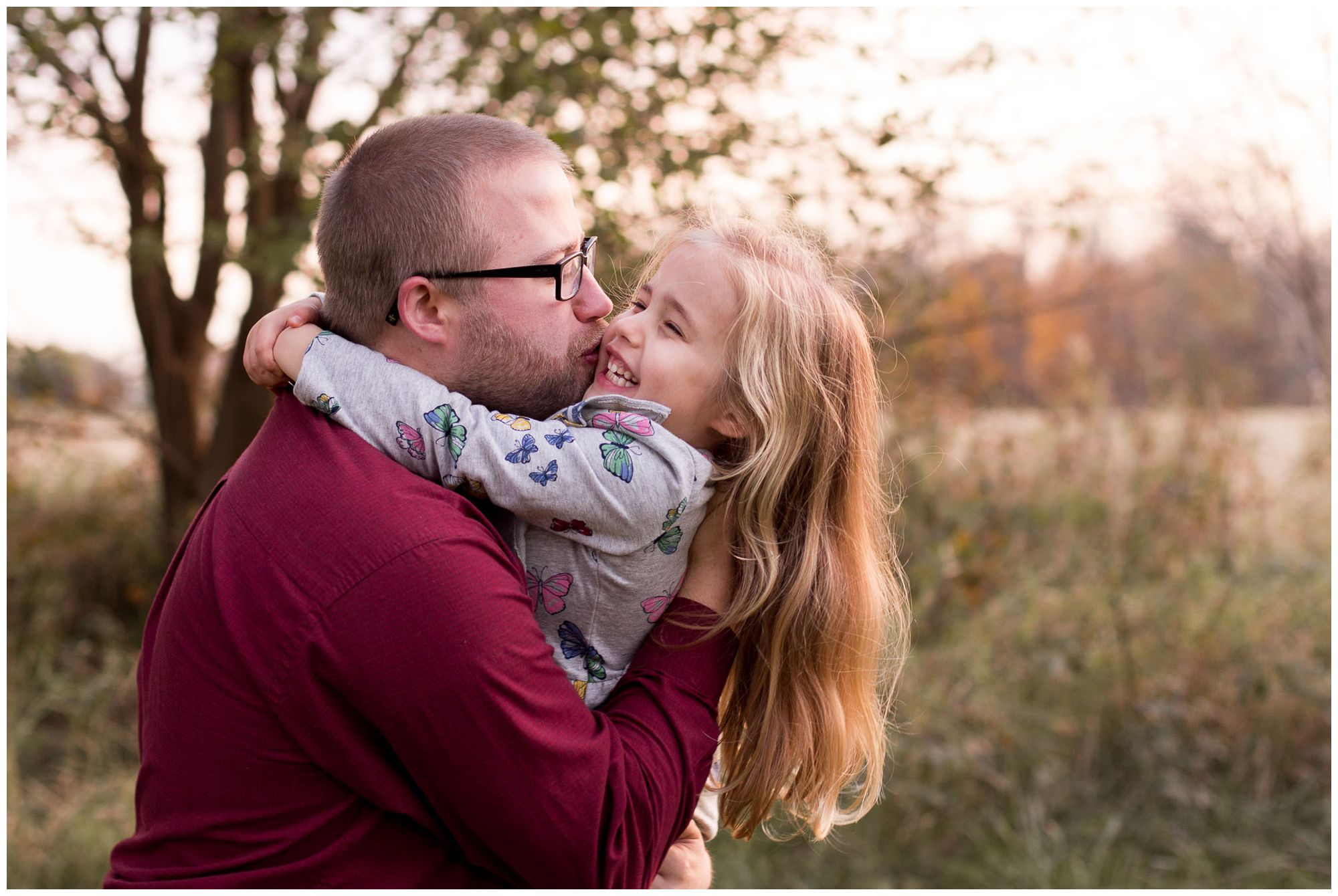 dad kisses daughter's cheek during Kokomo family session