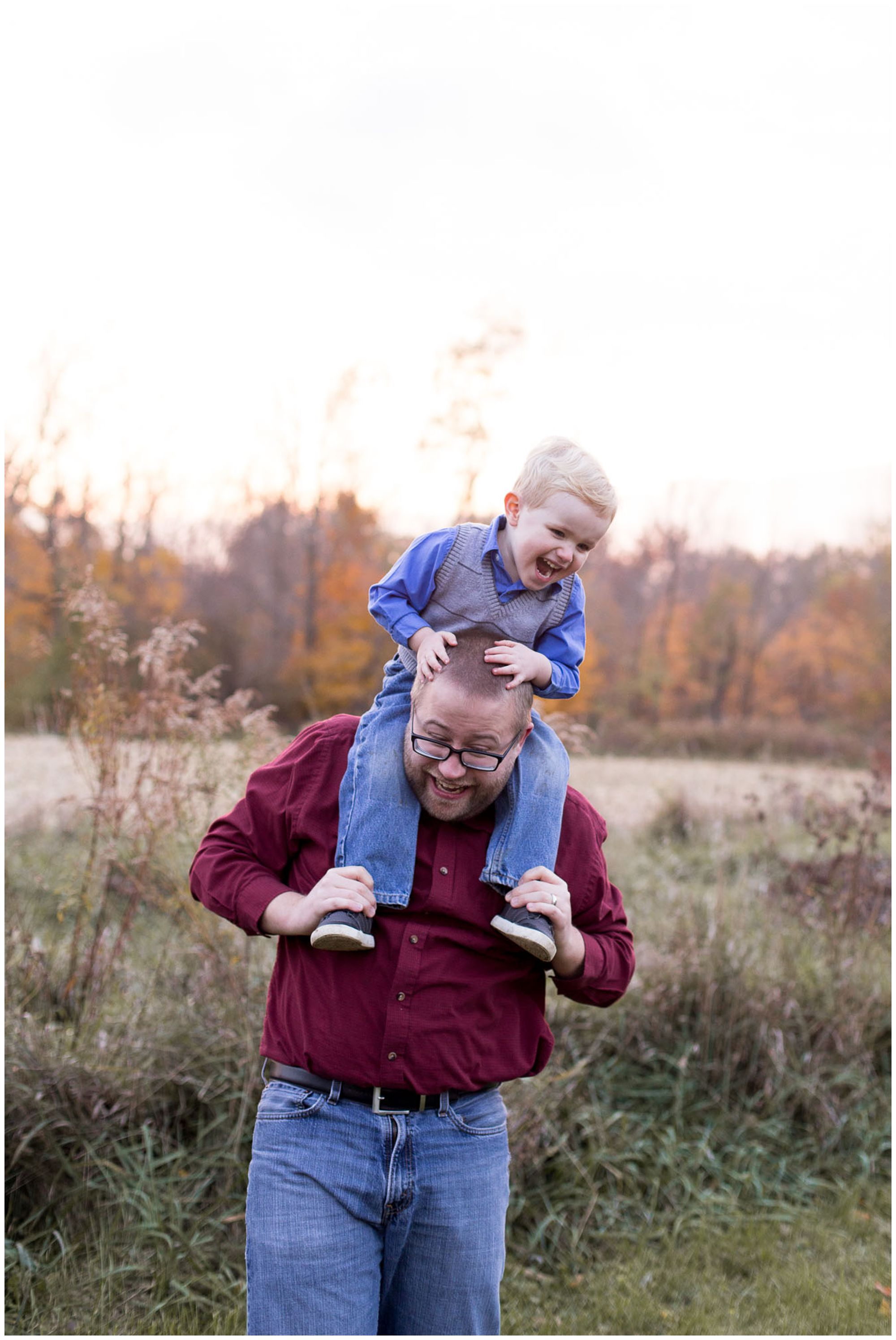 son sits on top of dad's shoulders during Kokomo family session