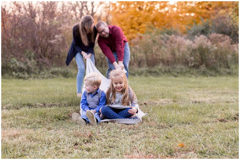 mom and dad drag kids on blanket as they giggle during Kokomo Indiana family session