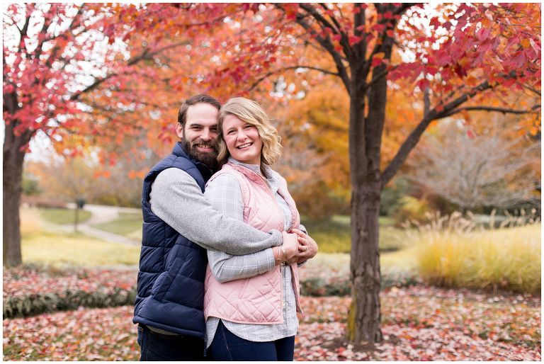 groom wraps arms around bride during fall engagement session at Headwaters Park in downtown Fort Wayne Indiana