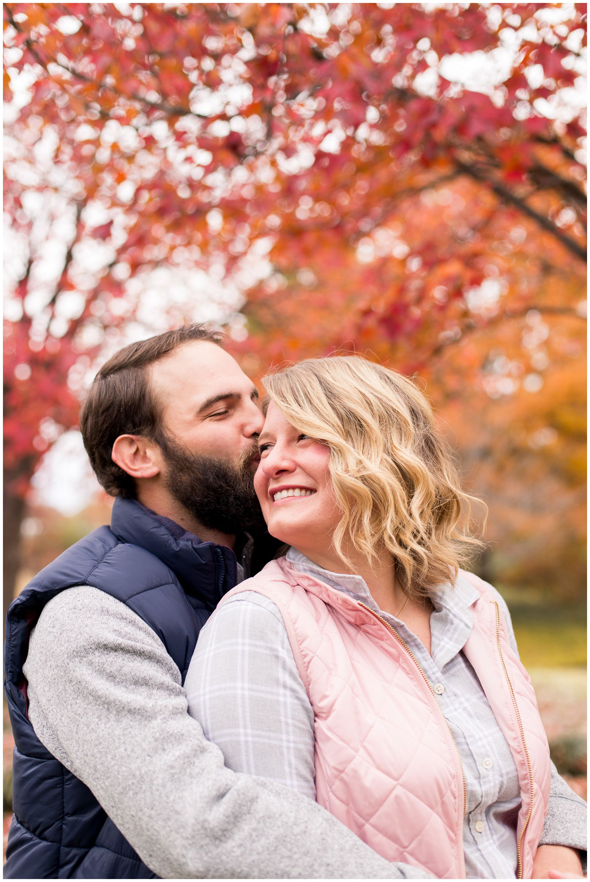 groom kisses bride's forehead during Fort Wayne engagement session at Headwaters Park
