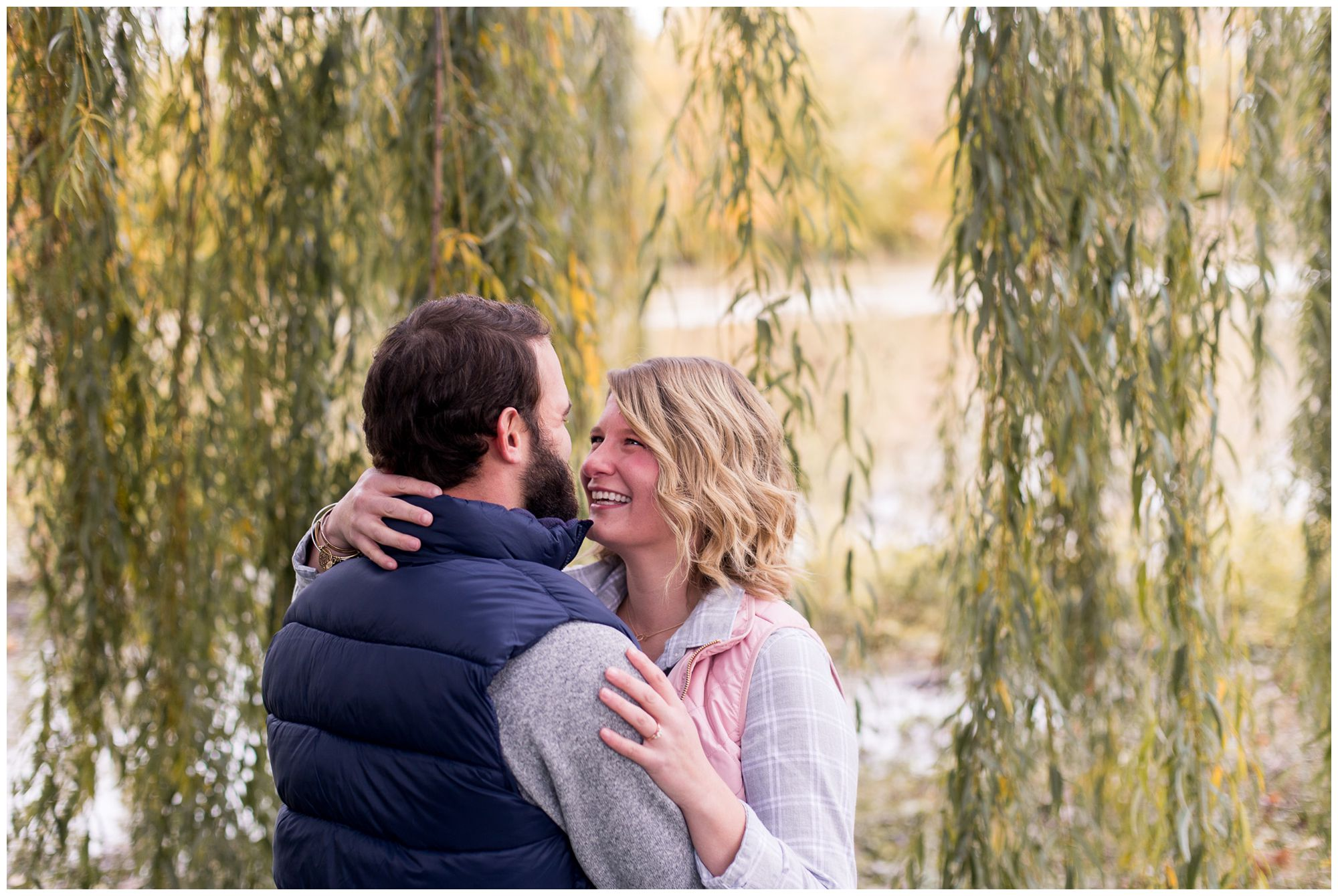 bride wraps hand around groom's neck during downtown Fort Wayne engagement session