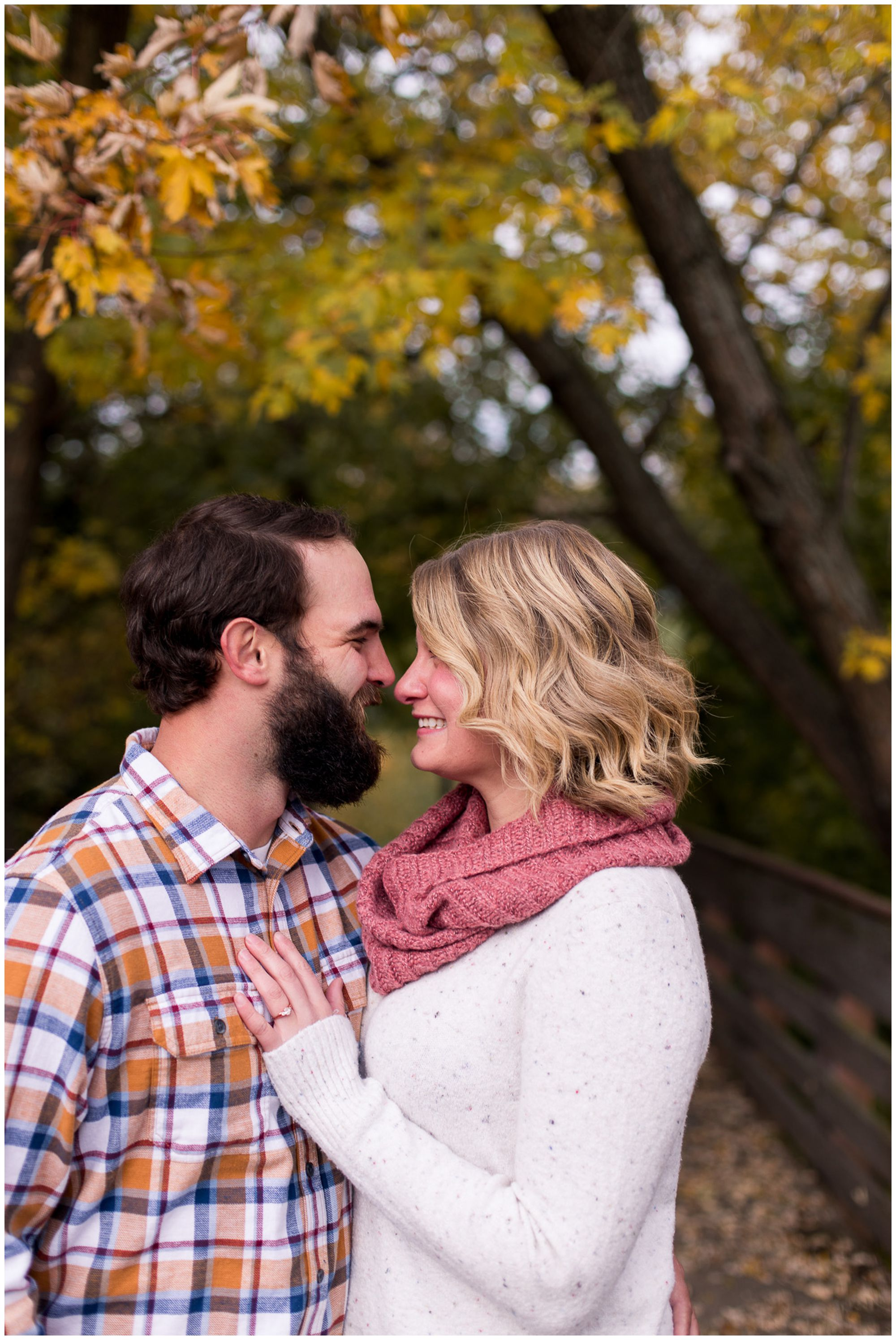 bride and groom snuggle in close during fall engagement session