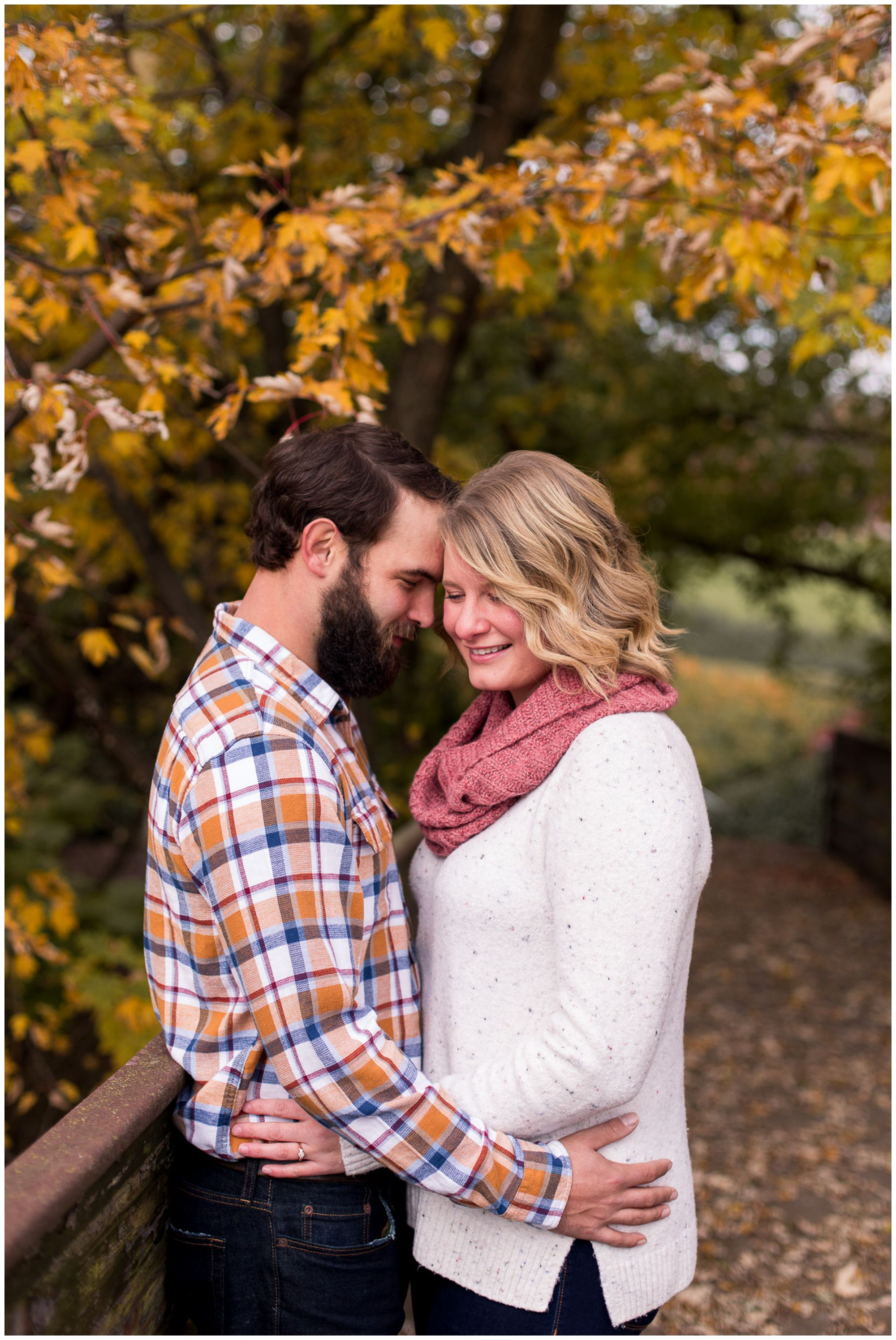 bride and groom smile with hands on waist during fall engagement session at Headwaters Park