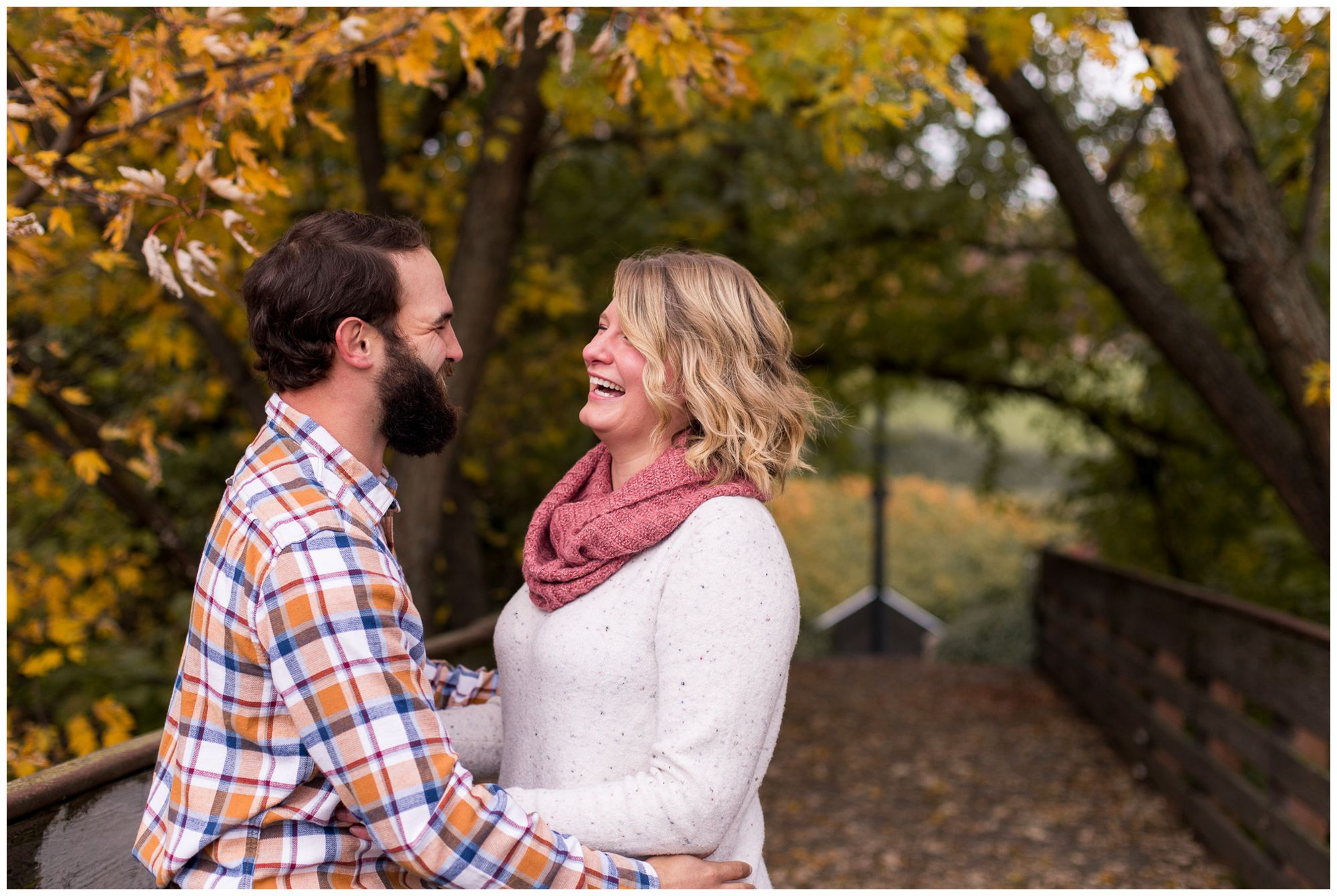 bride and groom laugh together during fall engagement session in downtown Fort Wayne