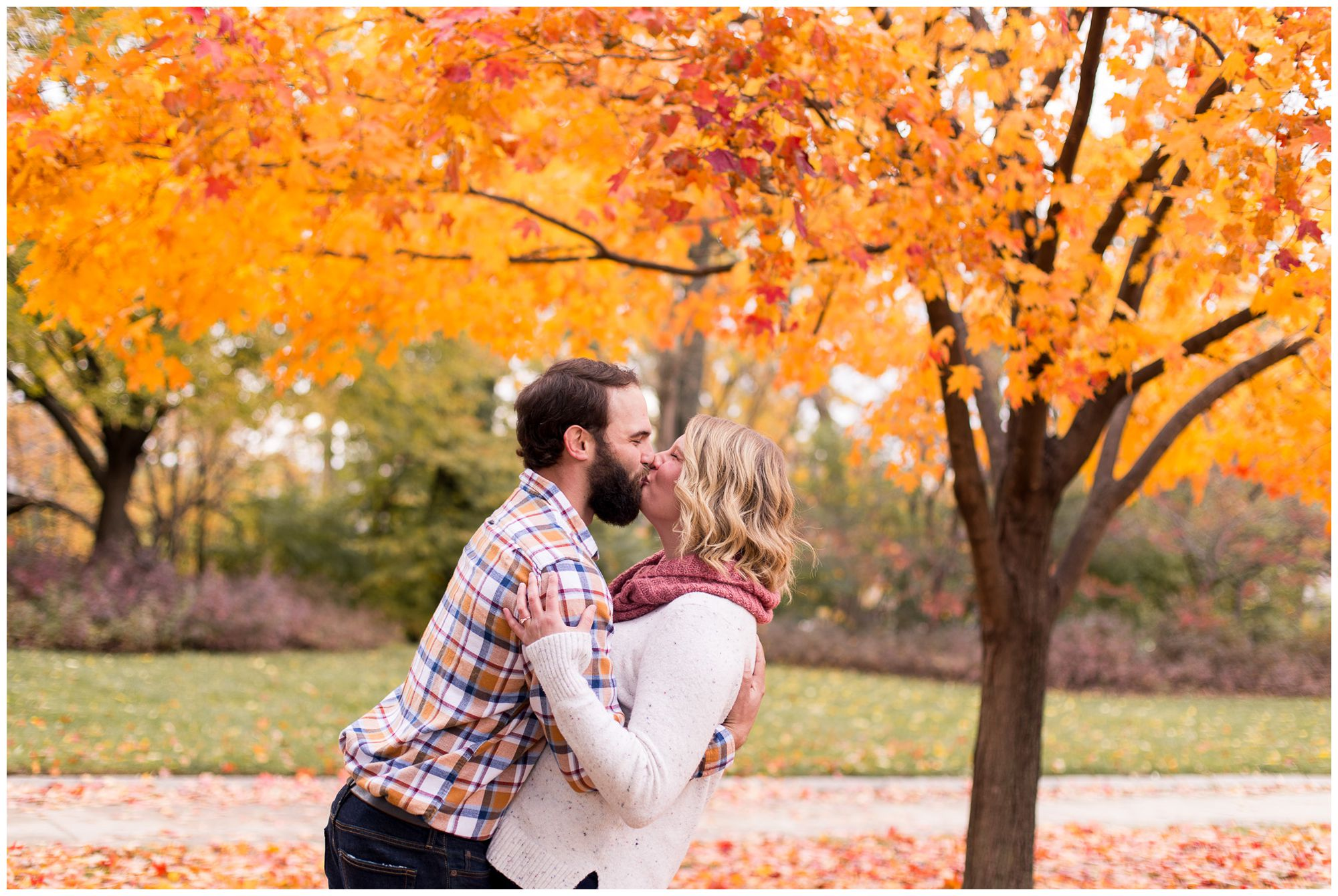 groom dips bride for kiss in front of fall foliage during engagement session at Headwaters Park