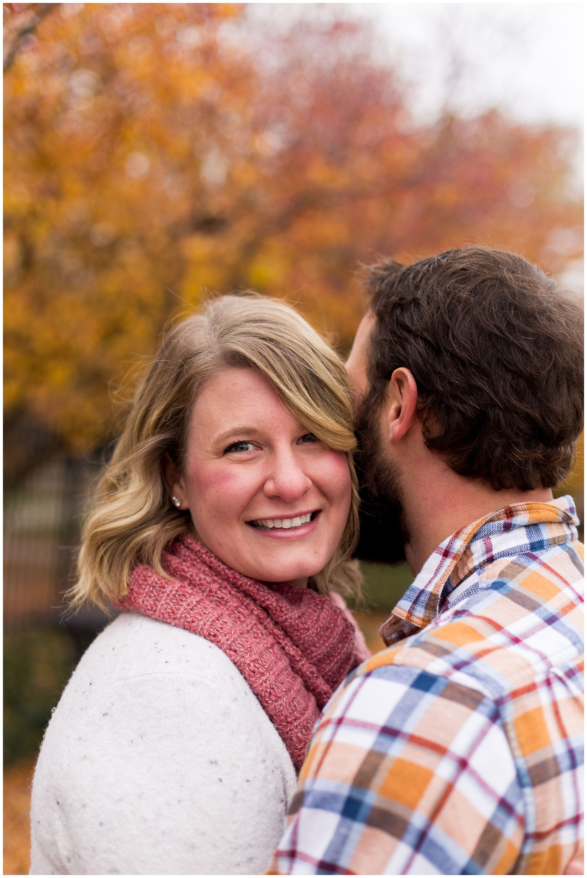 groom hugs bride while she smiles at the camera during fall engagement session