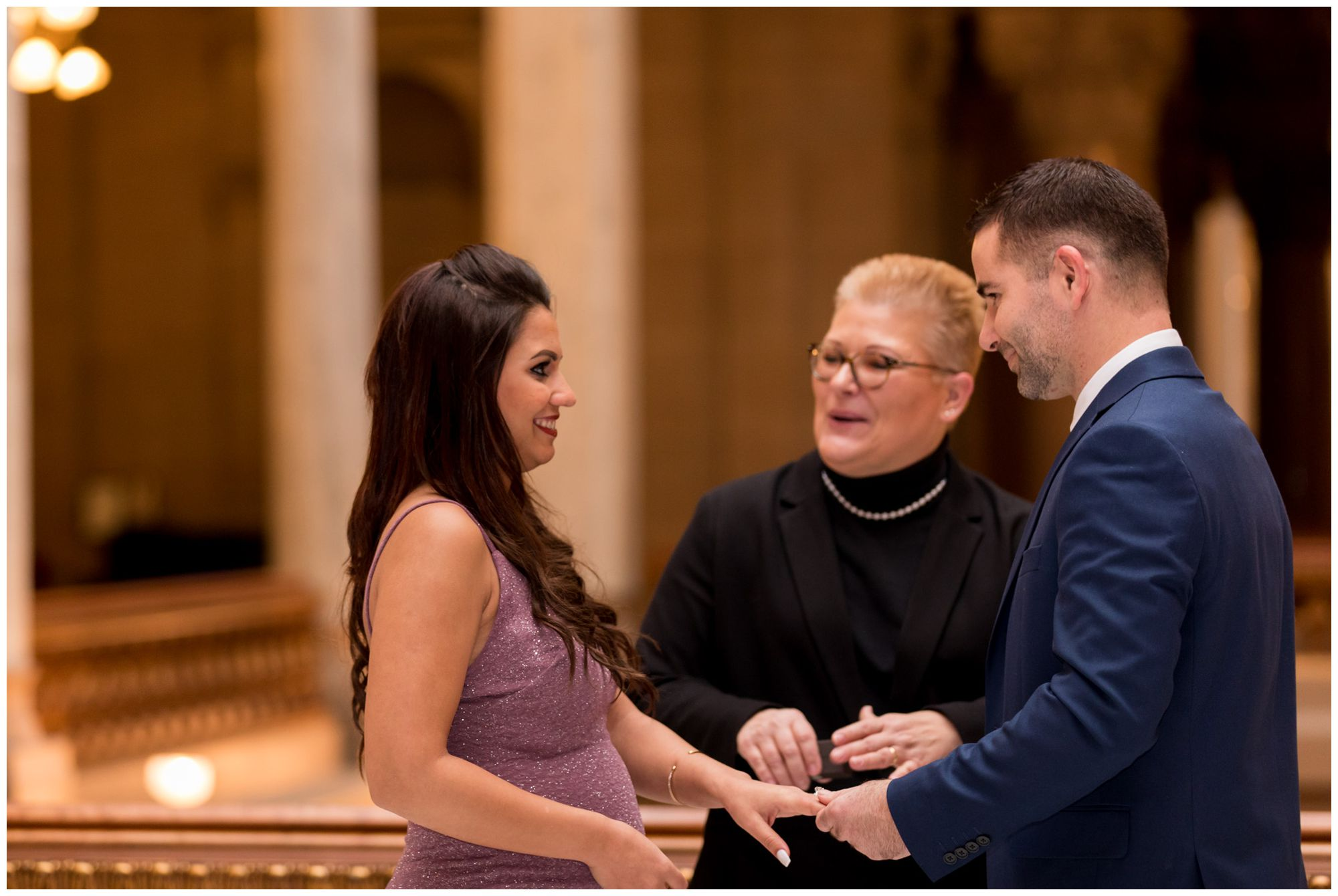 bride and groom exchange rings during Indiana Statehouse elopement ceremony in downtown Indianapolis