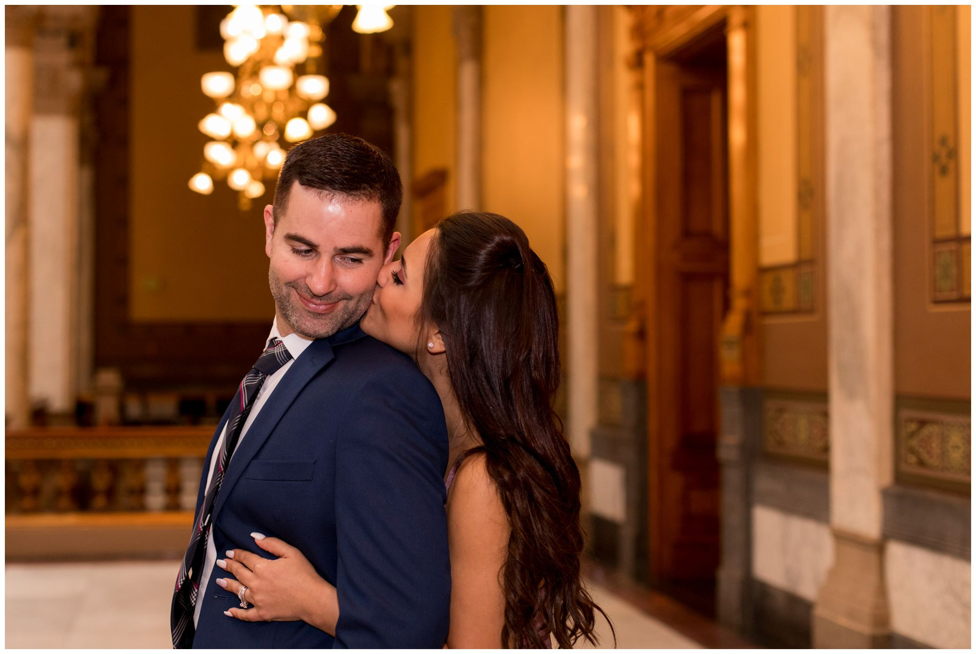 bride kisses groom's cheek at Indiana Statehouse after elopement ceremony in downtown Indianapolis