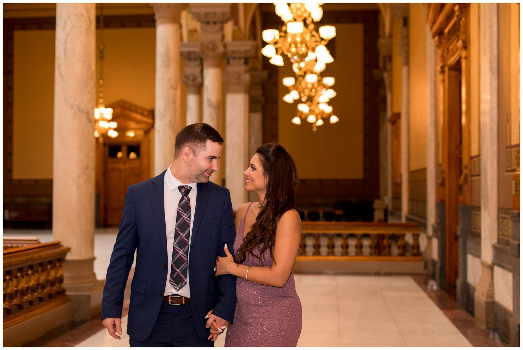 bride wraps arm around groom's arm and walk together after getting married at Indiana Statehouse in downtown Indianapolis