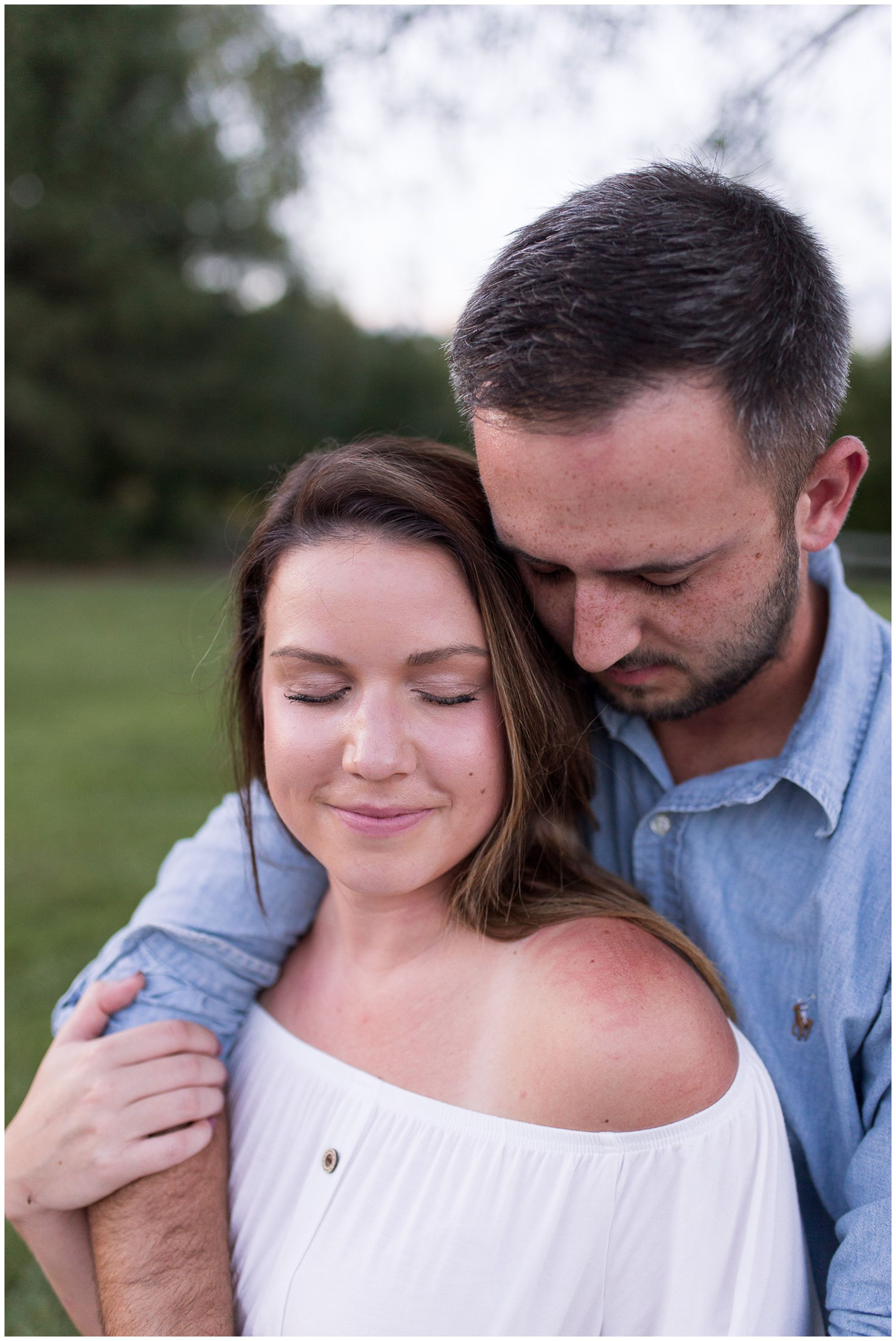 groom hugs bride from behind during Metea County Park engagement session in Fort Wayne Indiana