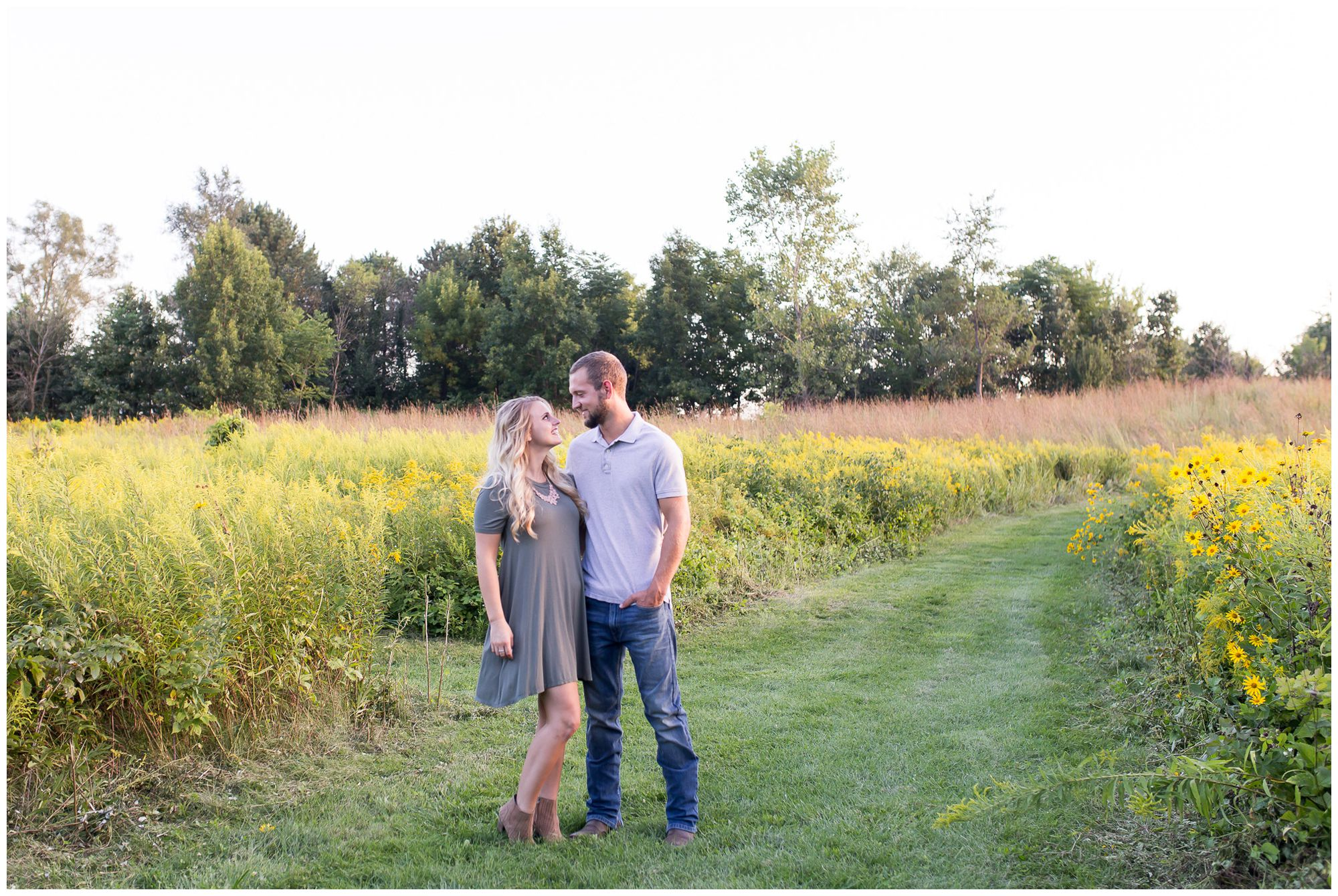 couple standing in open field during engagement session at Metea County Park in Fort Wayne
