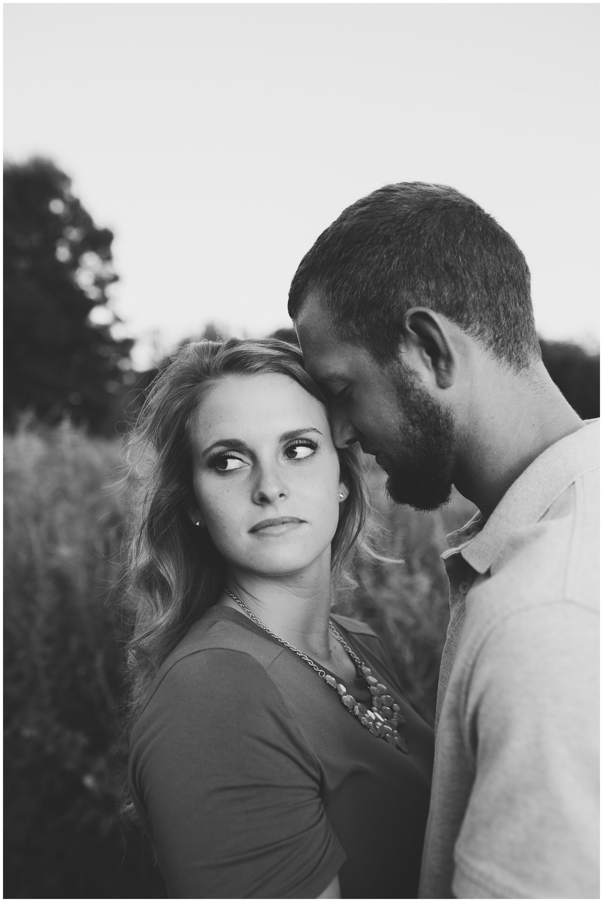 bride looks away with groom's forehead against hers during Fort Wayne engagement session at Metea County Park