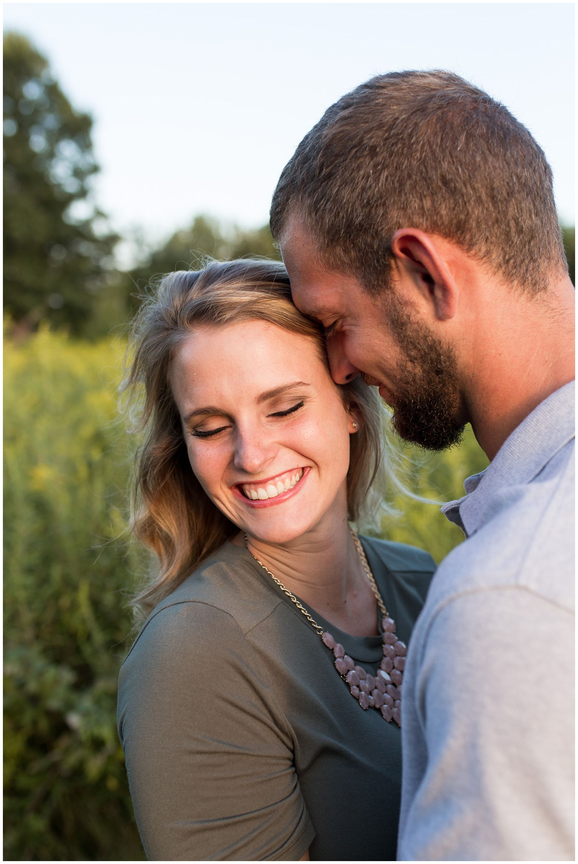 bride laughs with groom during Metea County Park engagement session in Fort Wayne Indiana