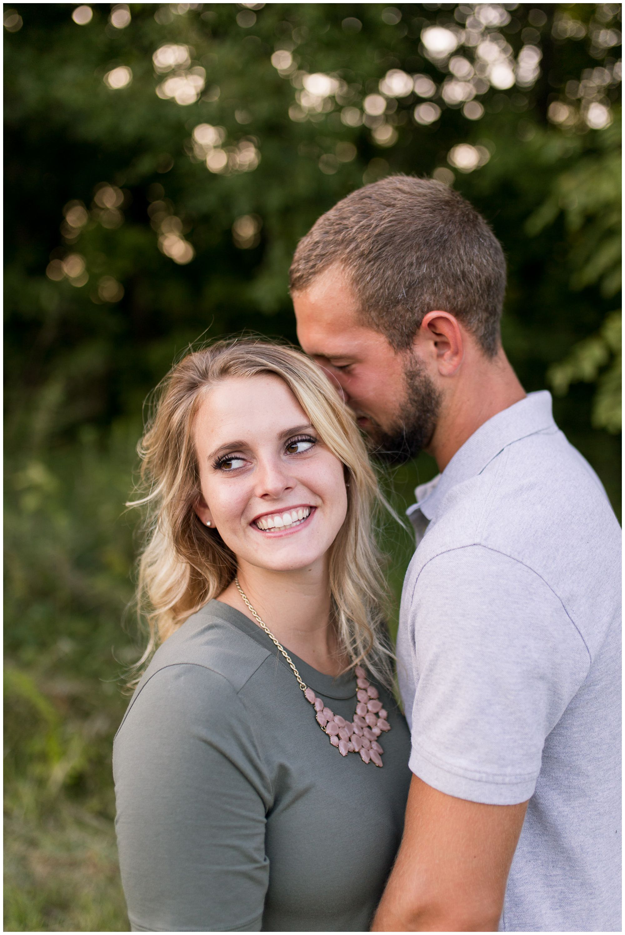 groom whispers in bride's ear during engagement session at Metea County Park in Fort Wayne