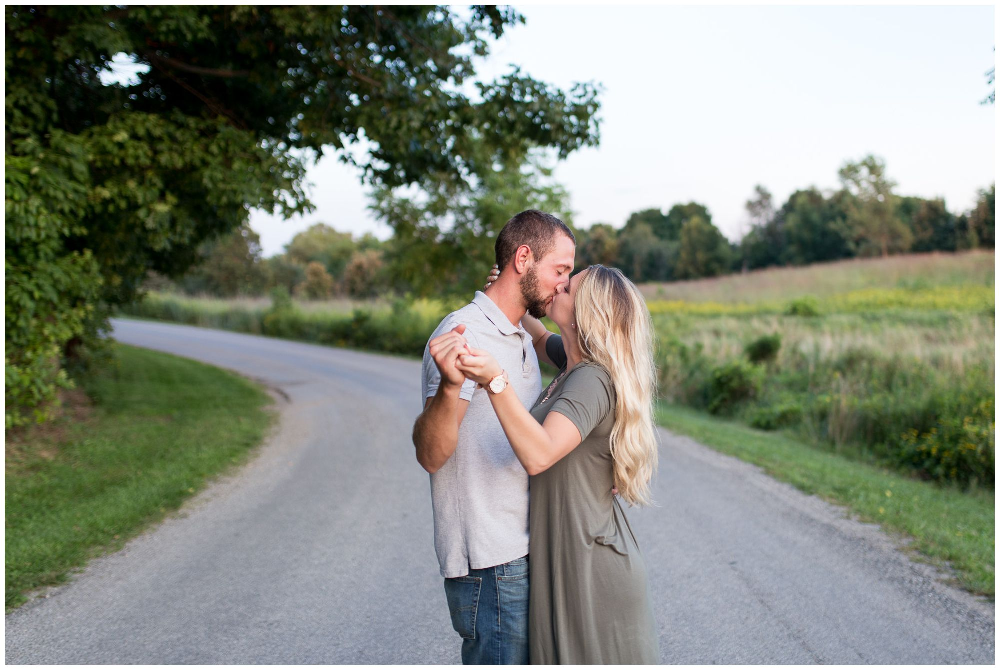 bride and groom kiss in road holding hands during Fort Wayne engagement session at Metea County Park