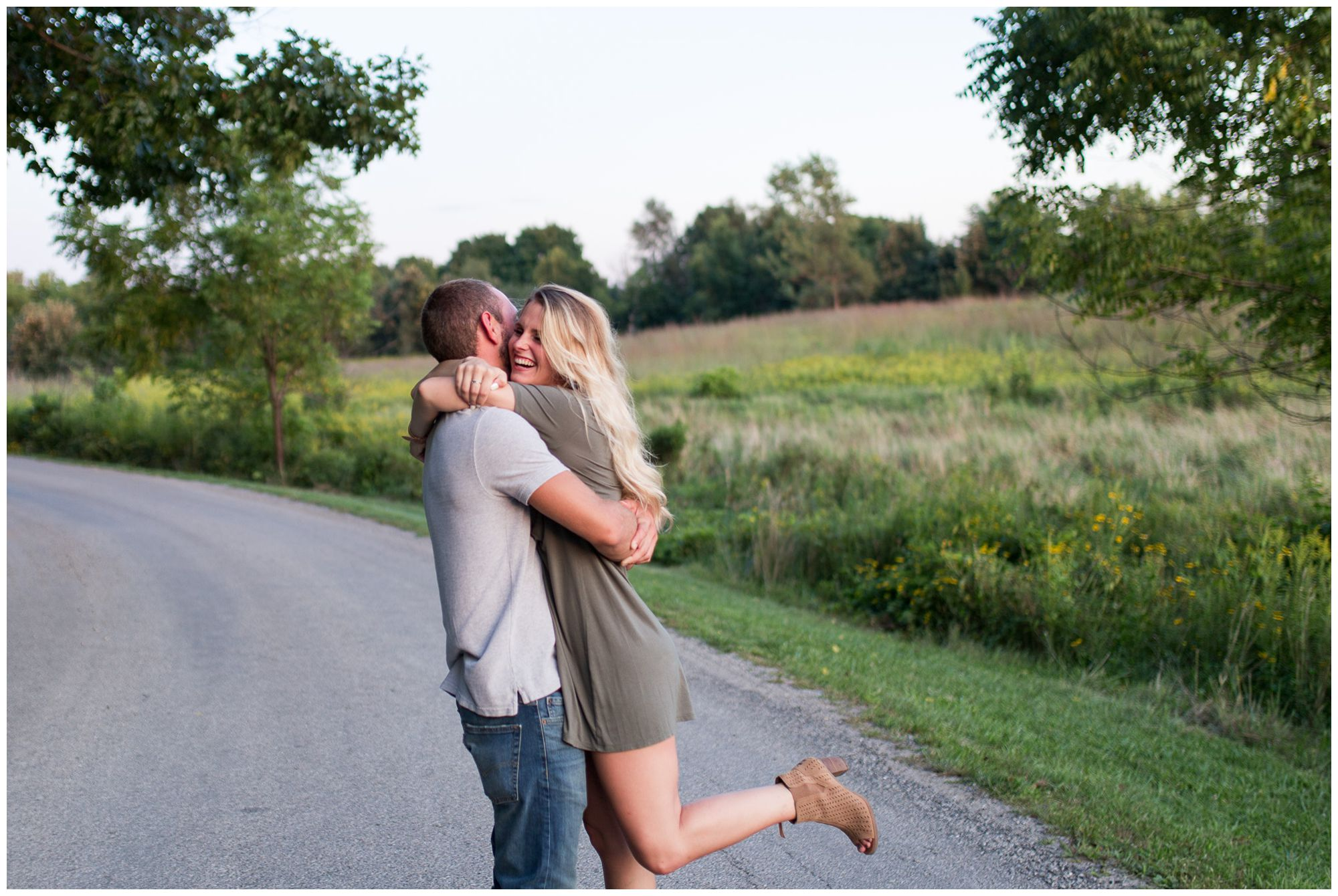 groom hugs and picks up bride during engagement session in Fort Wayne at Metea County Park