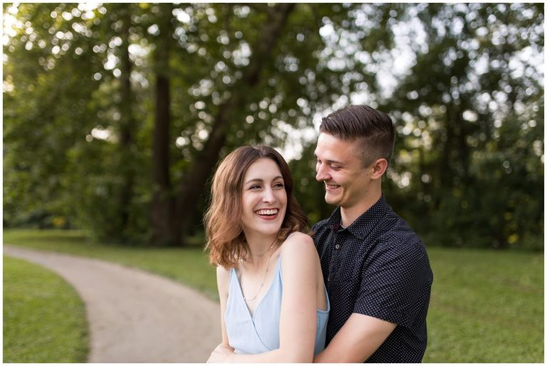 bride looks back and laughs with groom during engagement session at Fort Wayne's Foster Park