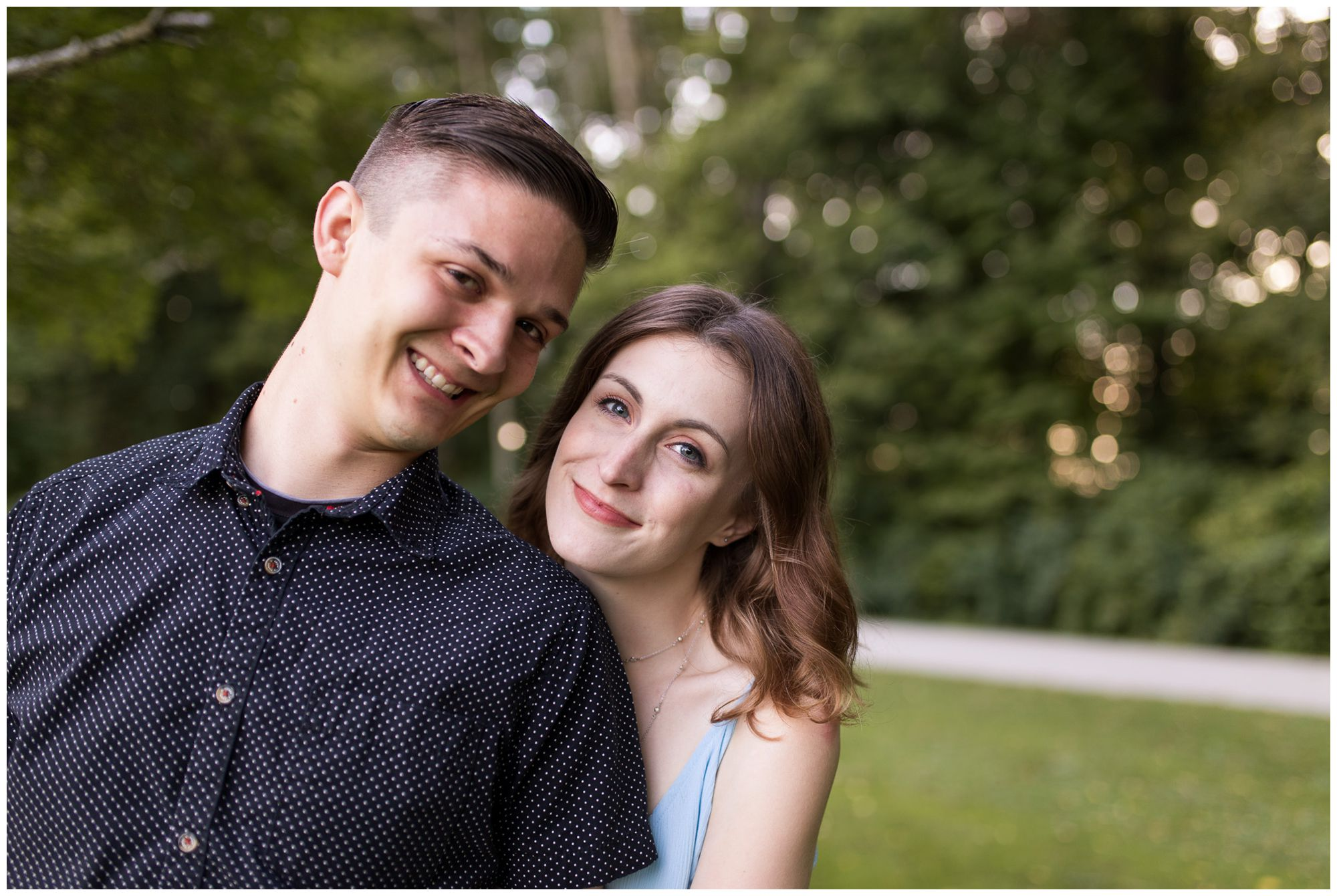 couple softly smiles during Fort Wayne engagement session at Foster Park