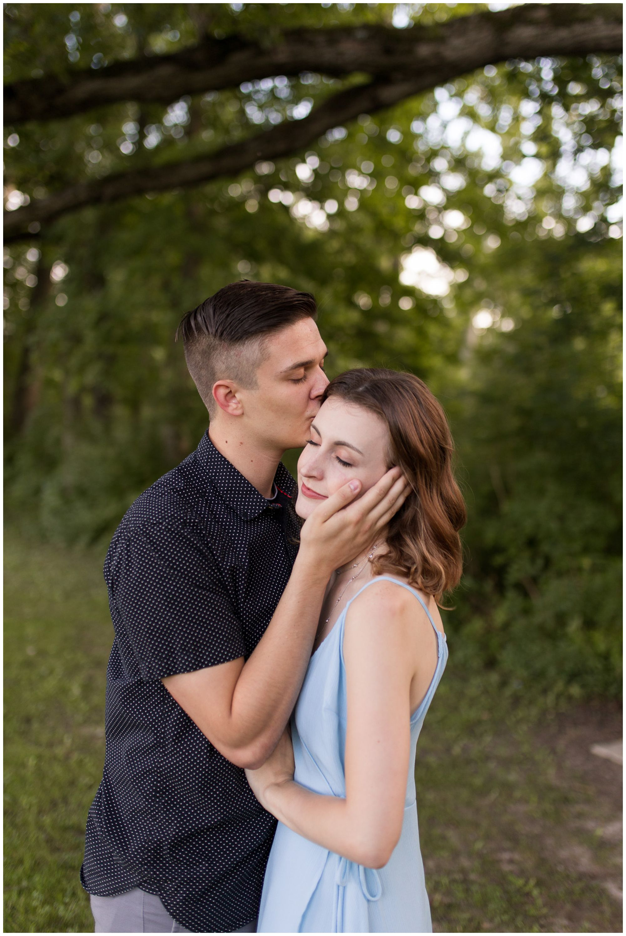 groom kisses bride's temple during Foster Park engagement session in Fort Wayne