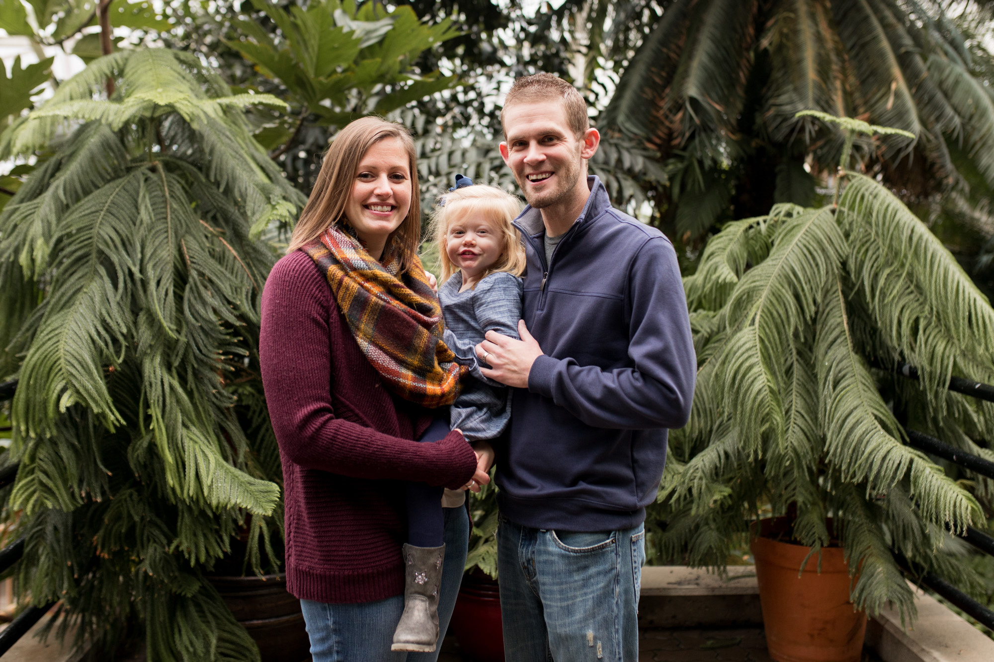 mom and dad hold baby during family session photography at Foellinger-Freimann Botanical Conservatory in Fort Wayne Indiana