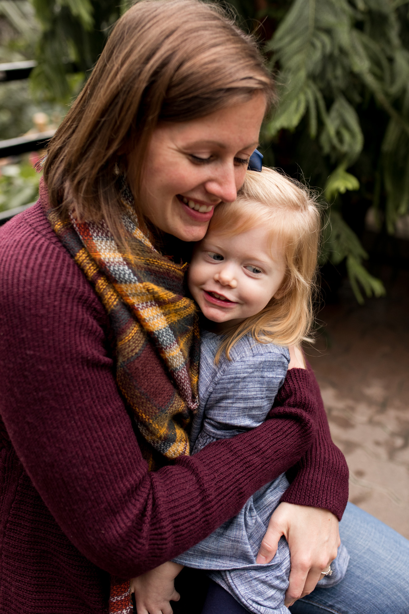 mom hugs daughter during family session at Foellinger-Freimann Botanical Conservatory in Fort Wayne Indiana