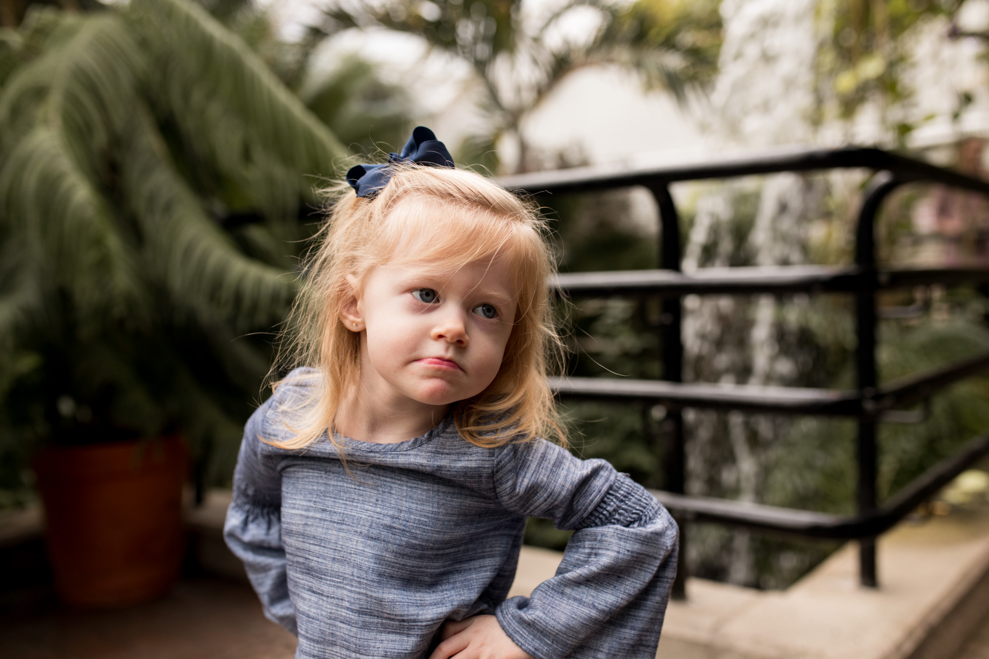 little girl poses during Fort Wayne family photography session at Foellinger-Freimann Botanical Conservatory