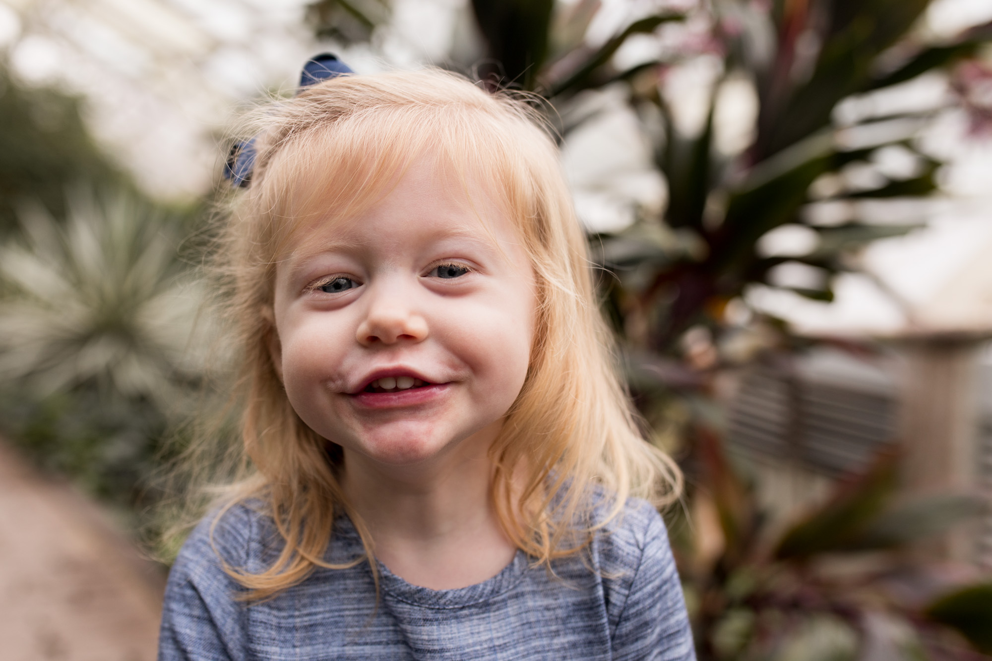 little girl smiles at camera at Foellinger-Freimann Botanical Conservatory during Fort Wayne family session
