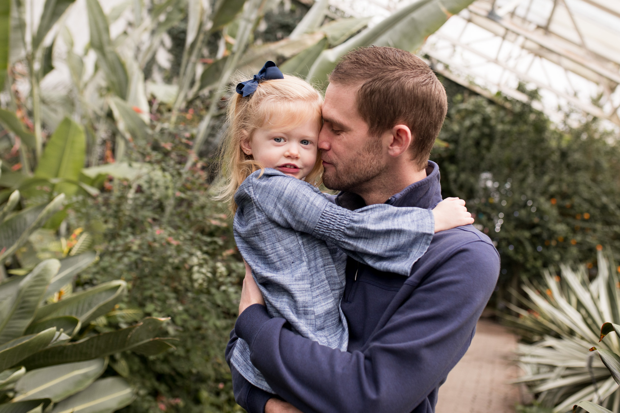 dad snuggles daughter's cheek during Foellinger-Freimann Botanical Conservatory family session in Fort Wayne Indiana