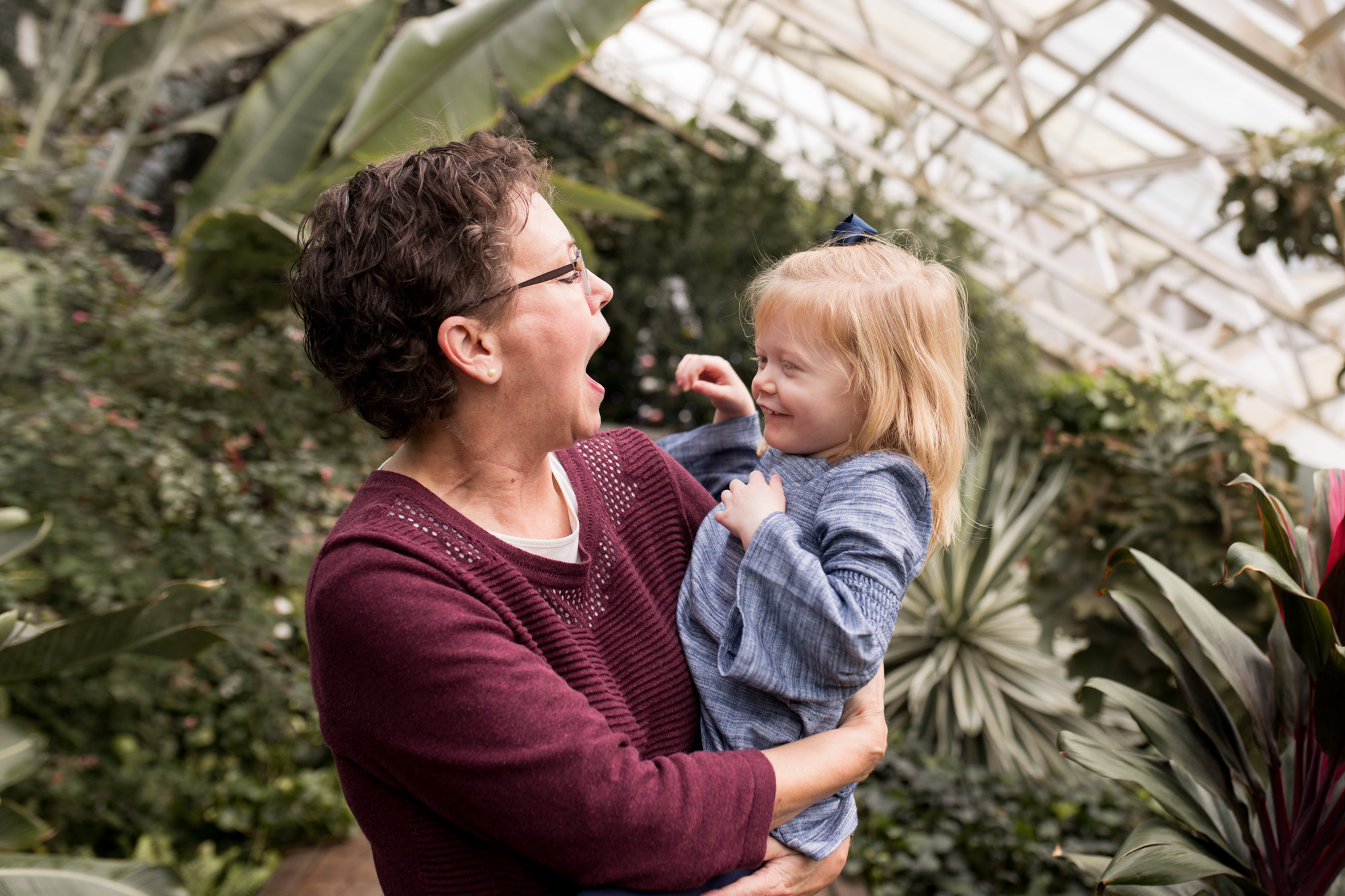 grandma laughs with granddaughter during Fort Wayne family photographer session at Foellinger-Freimann Botanical Conservatory